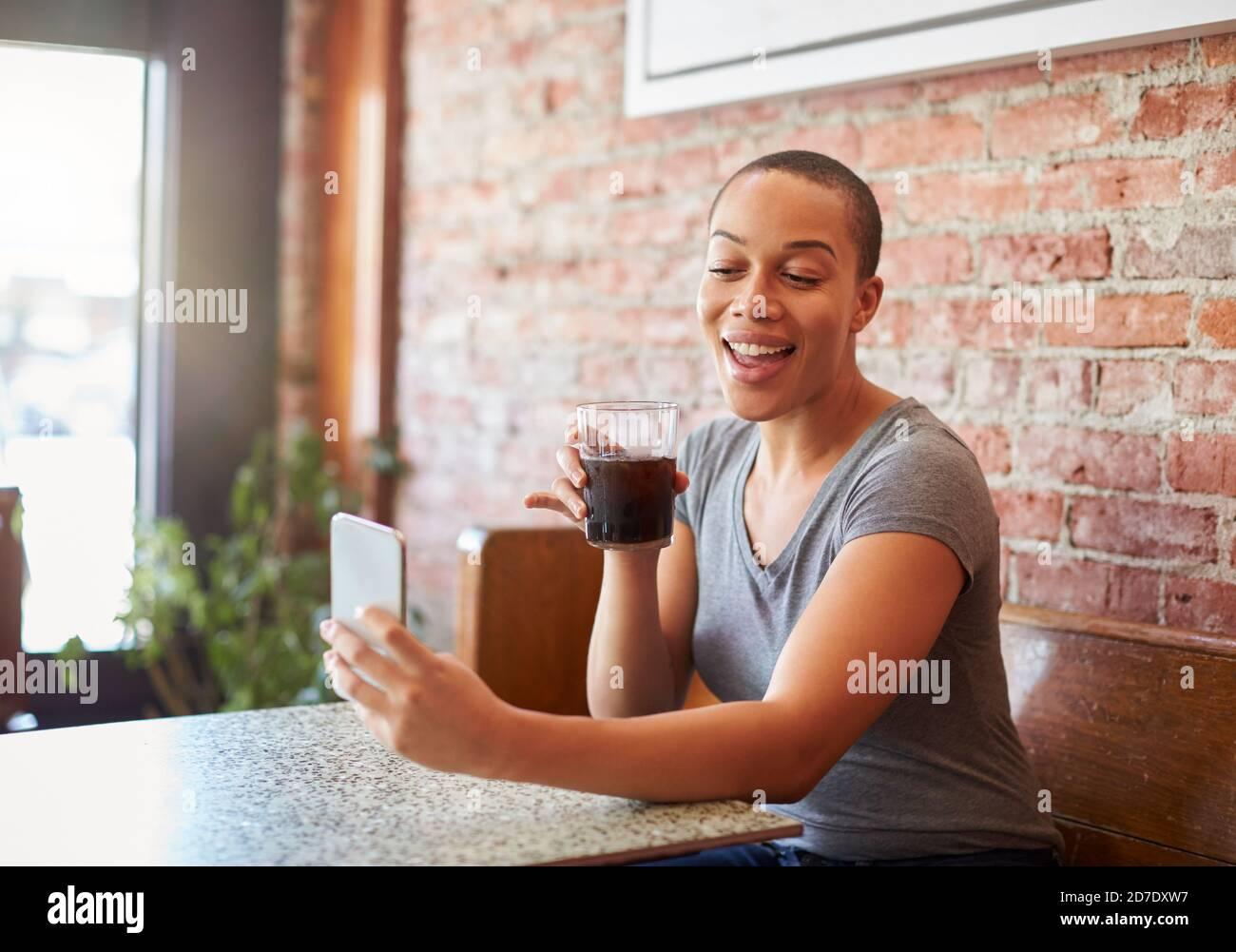 Femme effectuant un appel vidéo sur un téléphone portable assis dans un café Boutique Banque D'Images