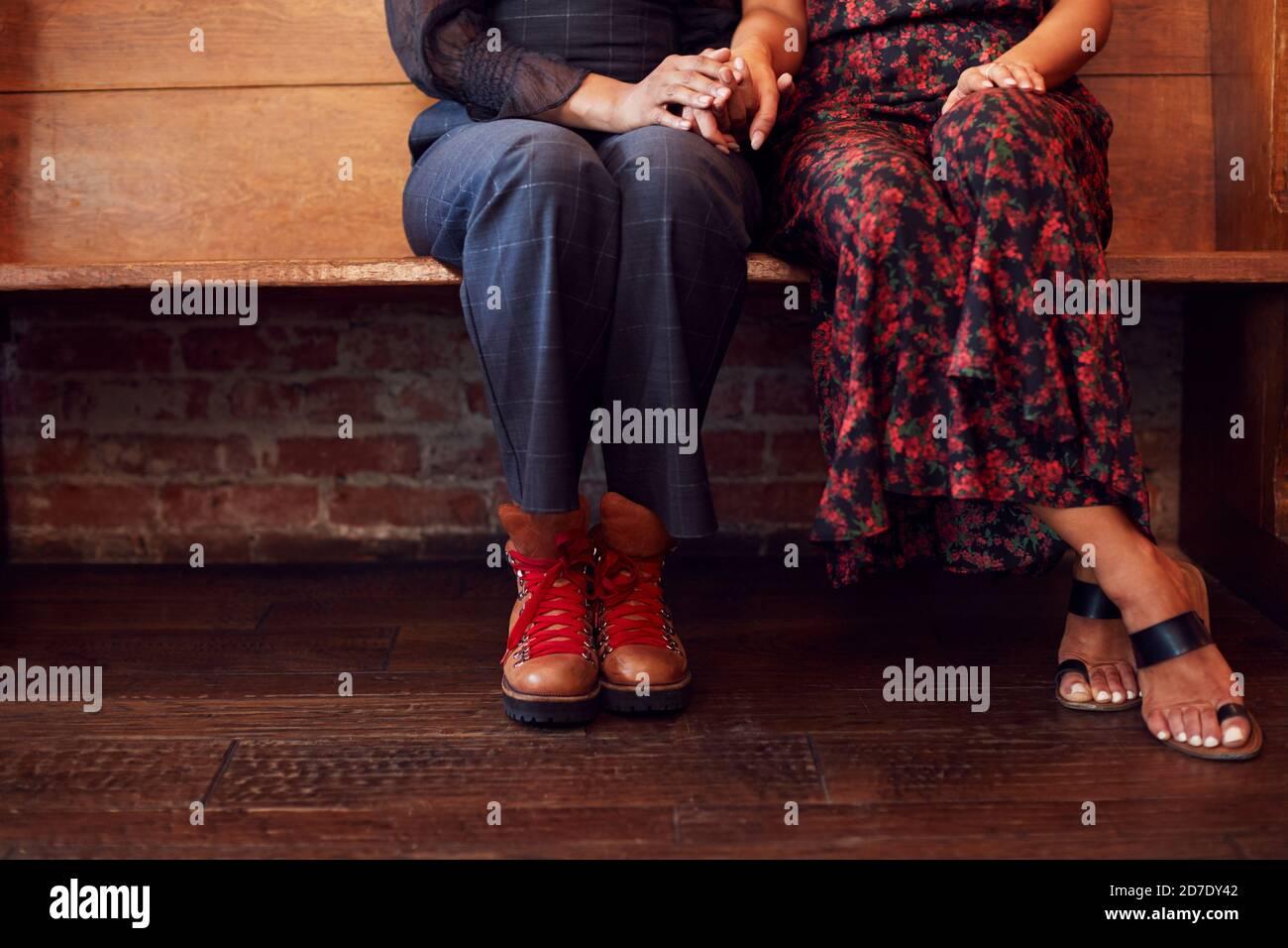 Gros plan sur les pieds du même sexe couple de femmes tenant Mains assises ensemble sur la banquette Banque D'Images