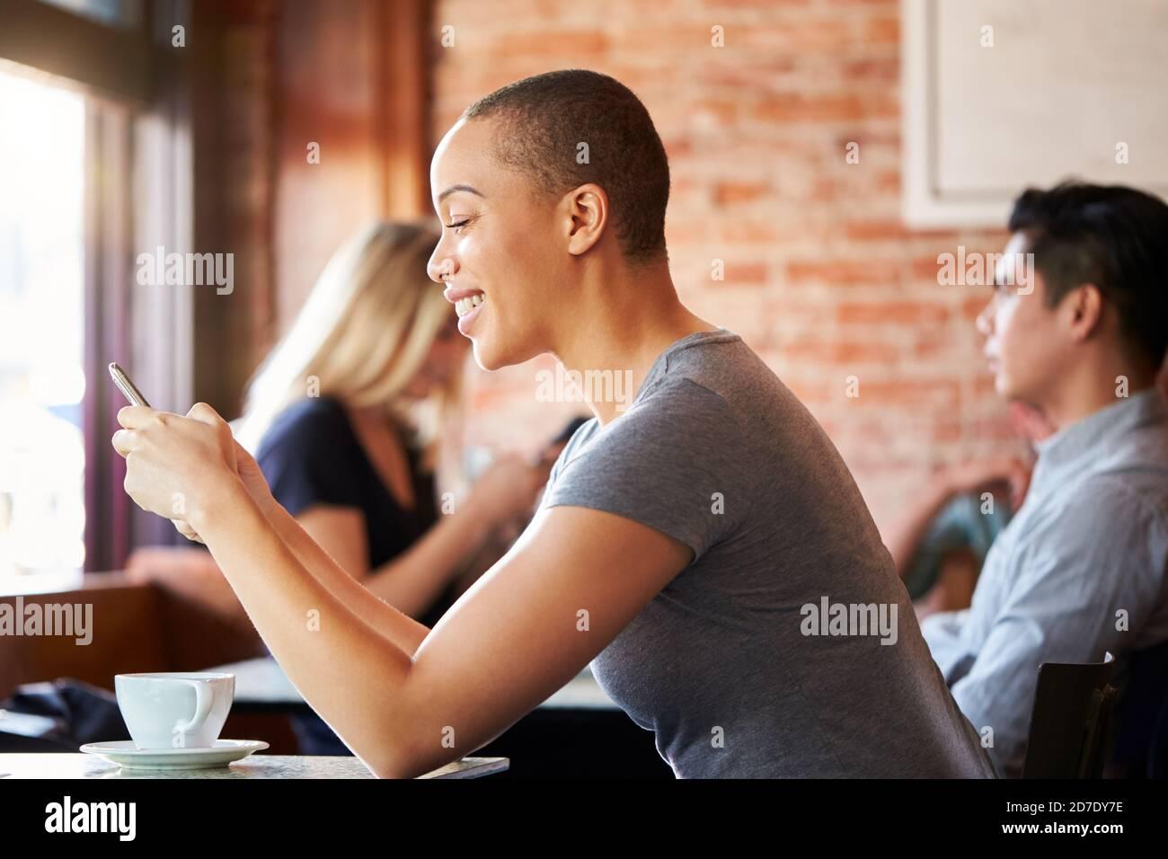 Femme utilisant un téléphone portable assis à une table dans un café Banque D'Images