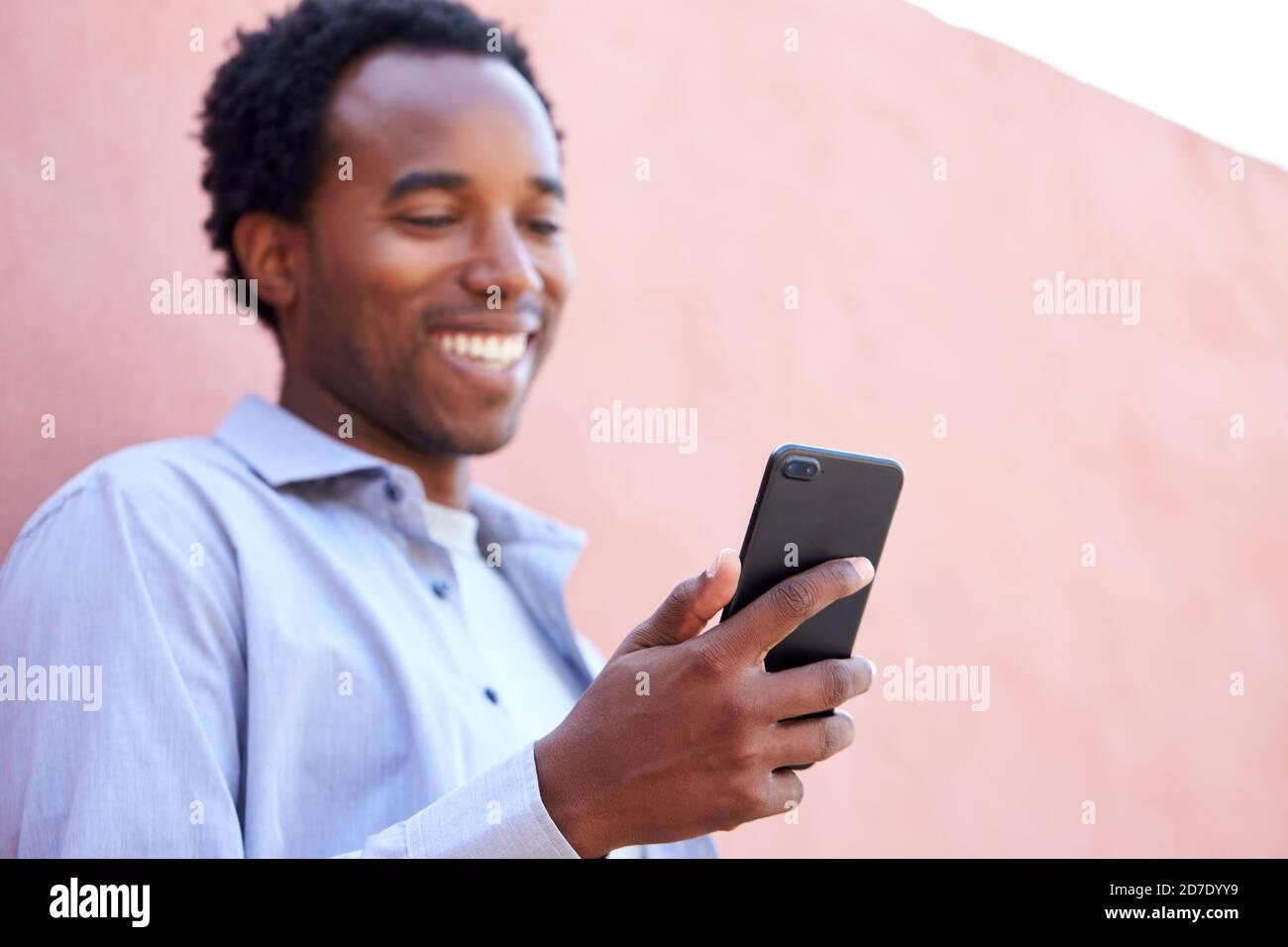 Portrait extérieur de l'homme utilisant le téléphone mobile dans la rue Se pencher contre le mur Banque D'Images
