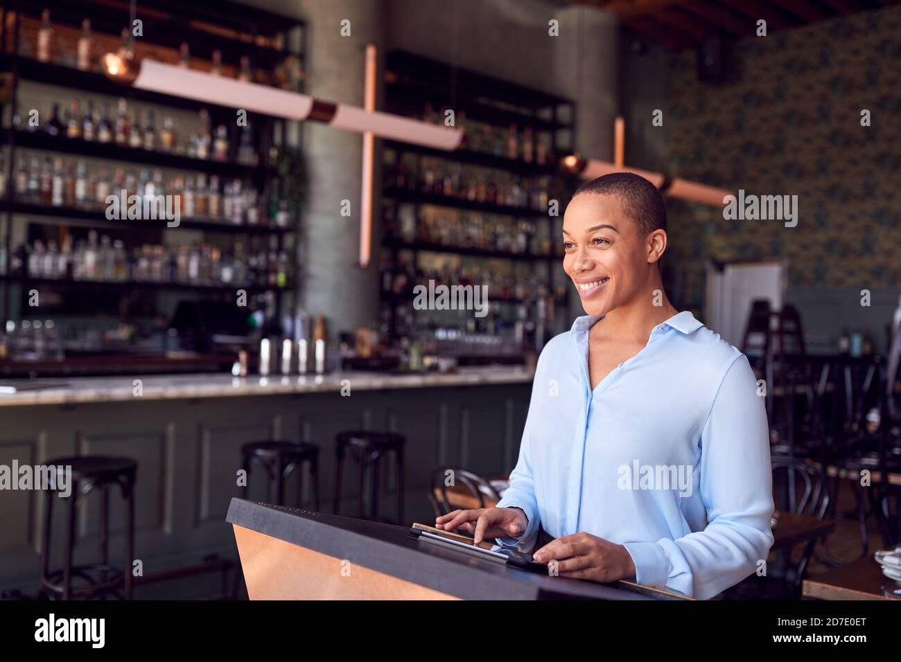 Femme propriétaire du bar-restaurant debout au comptoir en utilisant le numérique Tablette Banque D'Images