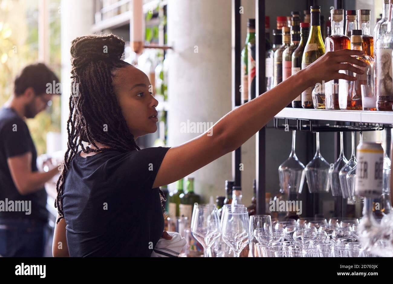 Femme Bartender organisant des bouteilles d'alcool derrière le bar Banque D'Images