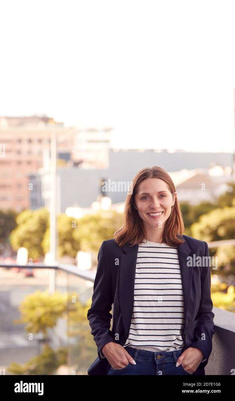 Portrait d'une femme d'affaires souriante debout à l'extérieur du bâtiment du bureau avec la ville Horizon en arrière-plan Banque D'Images