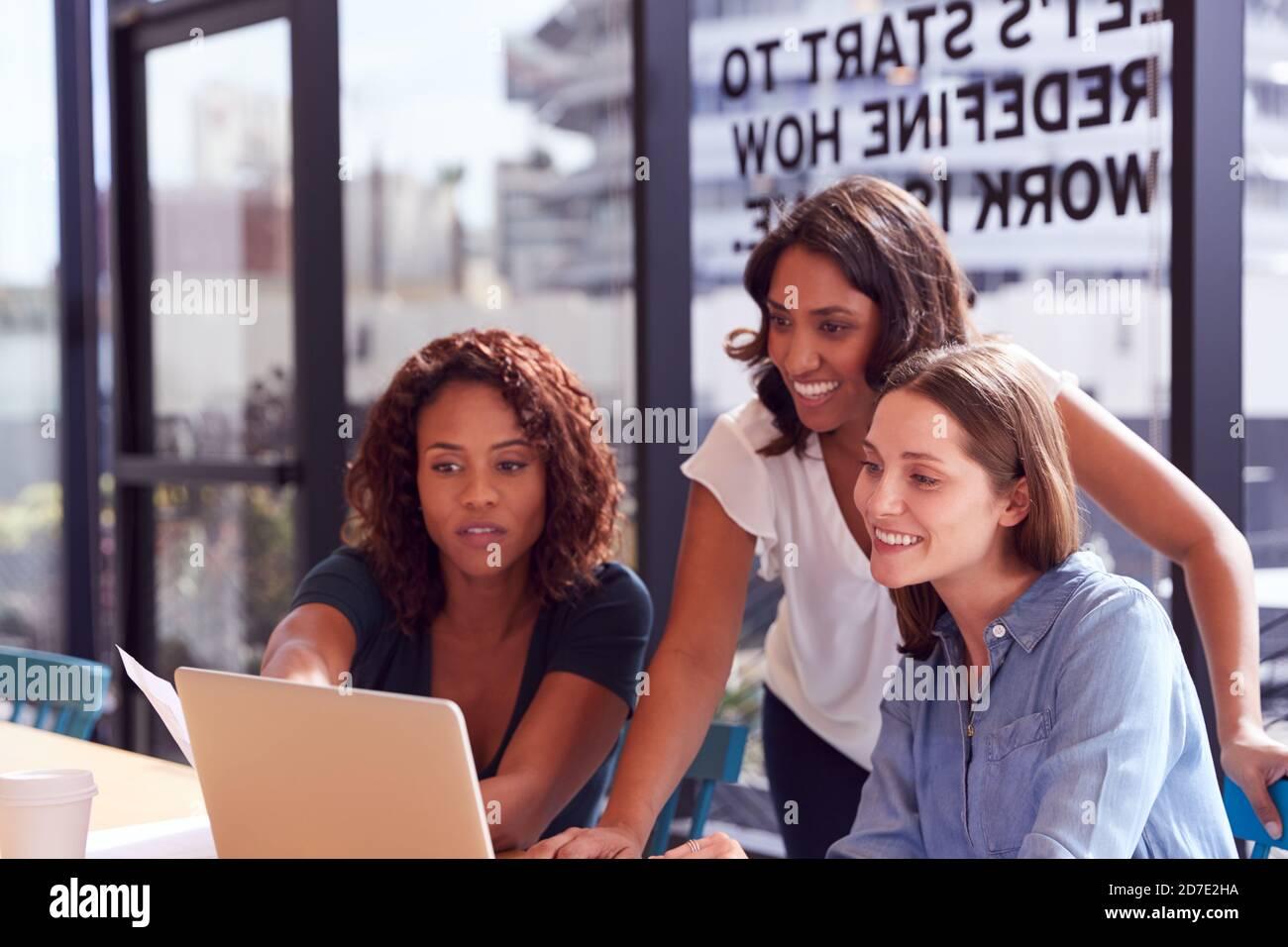 Trois femmes d'affaires avec ordinateur portable au bureau par fenêtre au bureau Collaborer sur le projet ensemble Banque D'Images