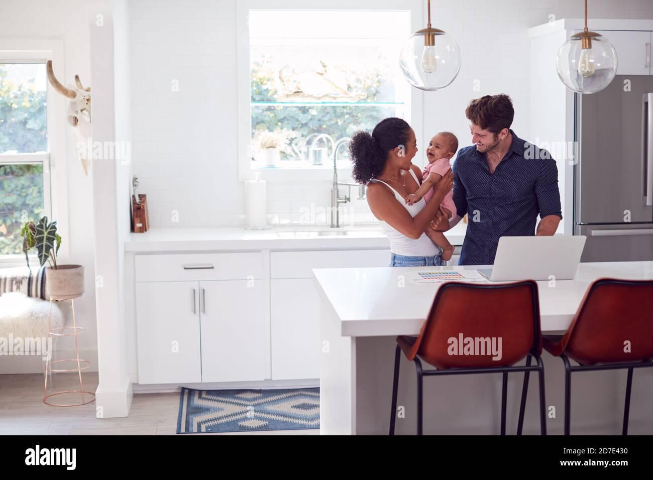 Famille avec bébé fille dans la cuisine utilisant un ordinateur portable sur le comptoir Banque D'Images