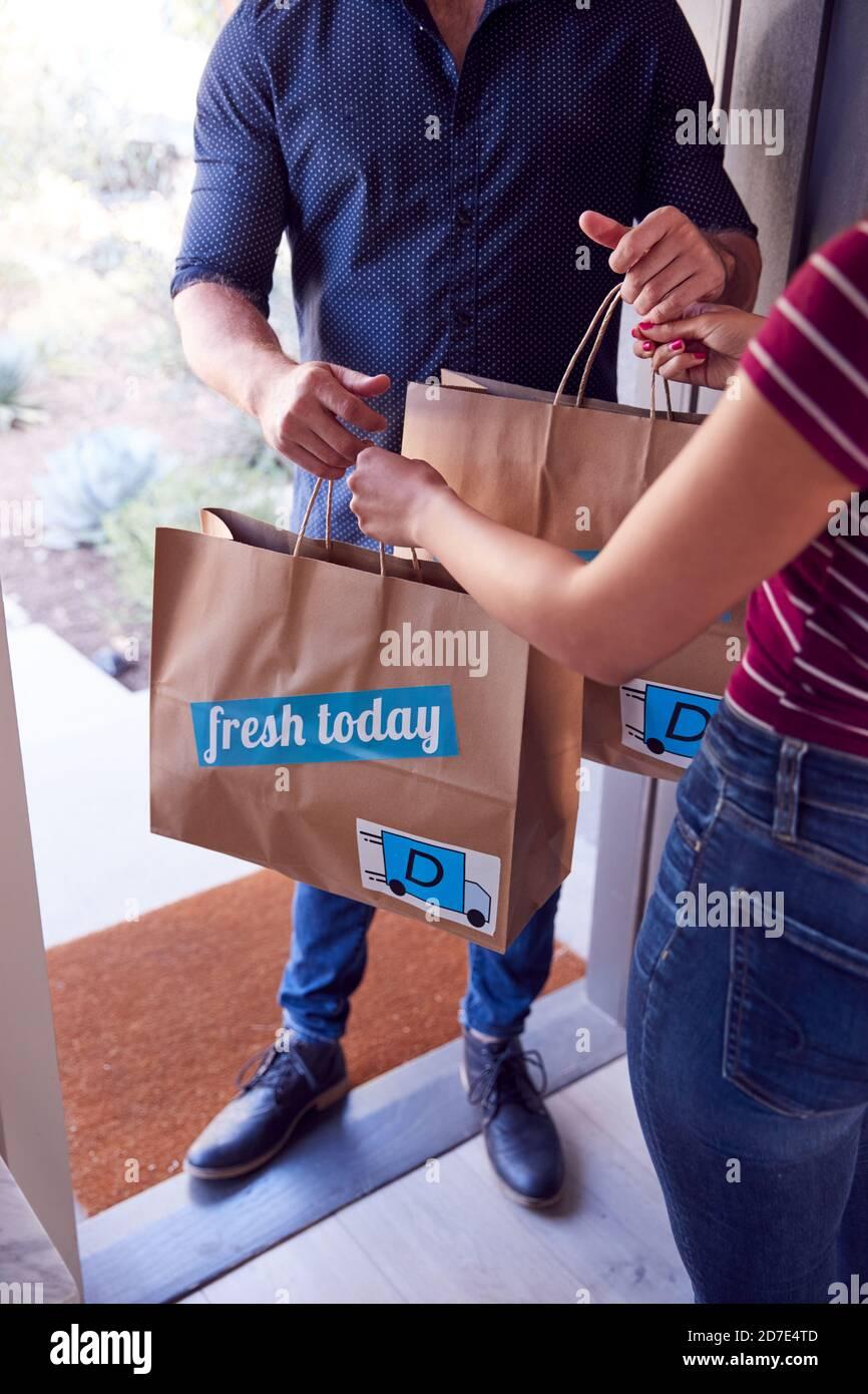 Gros plan sur le service de livraison à domicile chauffeur distribuant des aliments à emporter Sacs à la cliente féminine à la maison Banque D'Images