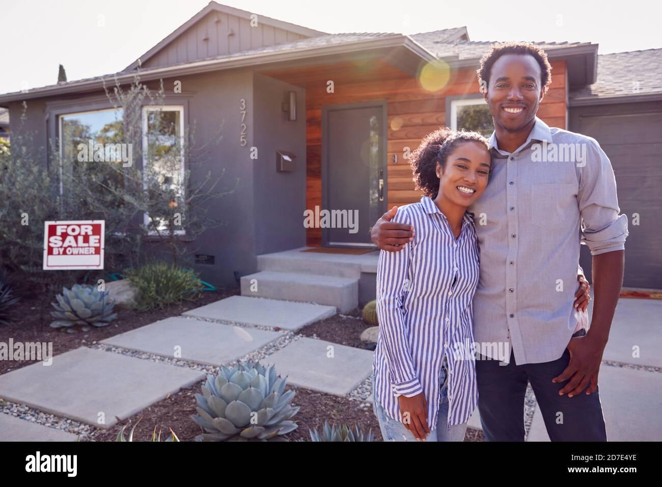 Portrait d'un couple souriant debout à l'extérieur devant la maison Avec enseigne à vendre dans le jardin Banque D'Images