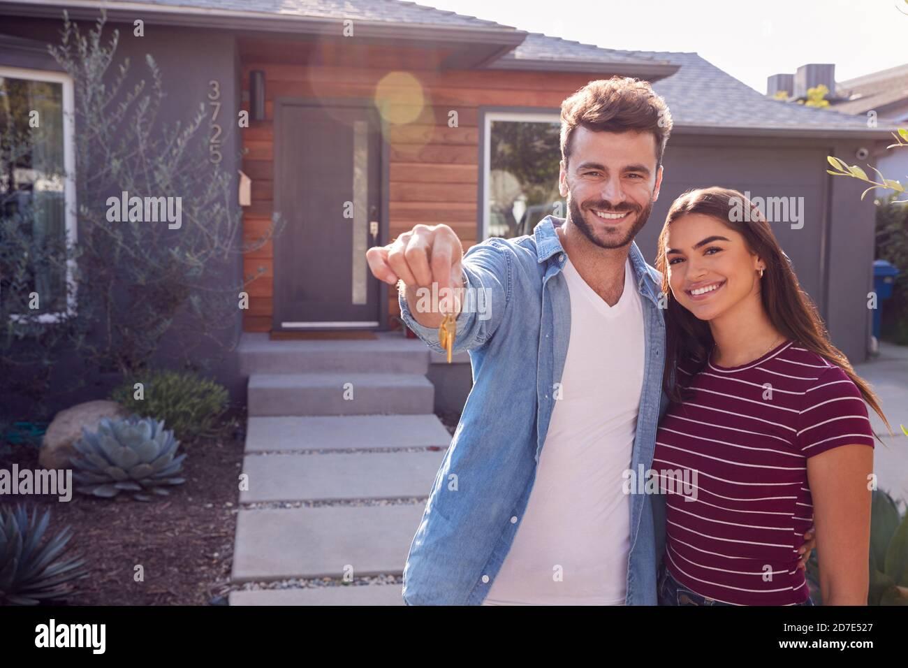 Portrait de couple debout à l'extérieur devant la maison avec Pour la vente Sign In Garden Holding Keys Banque D'Images