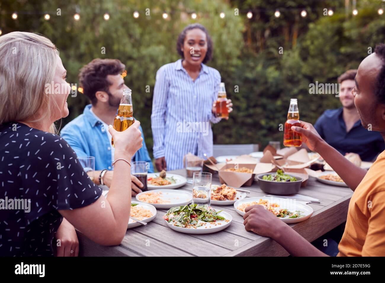 Amis multiculturels à la maison autour de la table faire UN toast comme Ils aiment manger à Summer Garden Party Banque D'Images