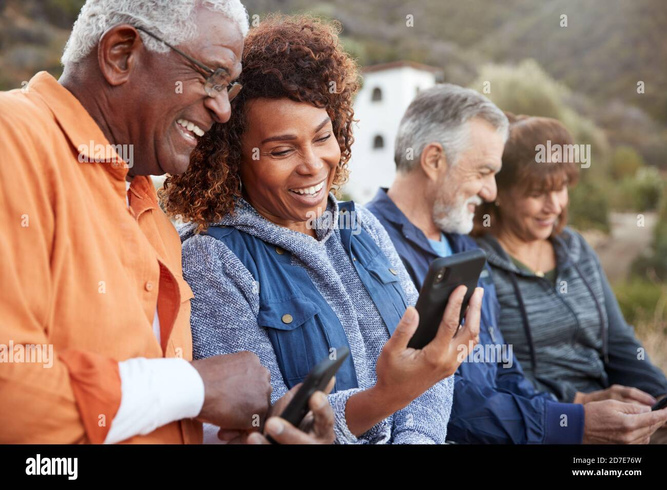 Groupe d'amis seniors en randonnée à la campagne Téléphones mobiles ensemble Banque D'Images