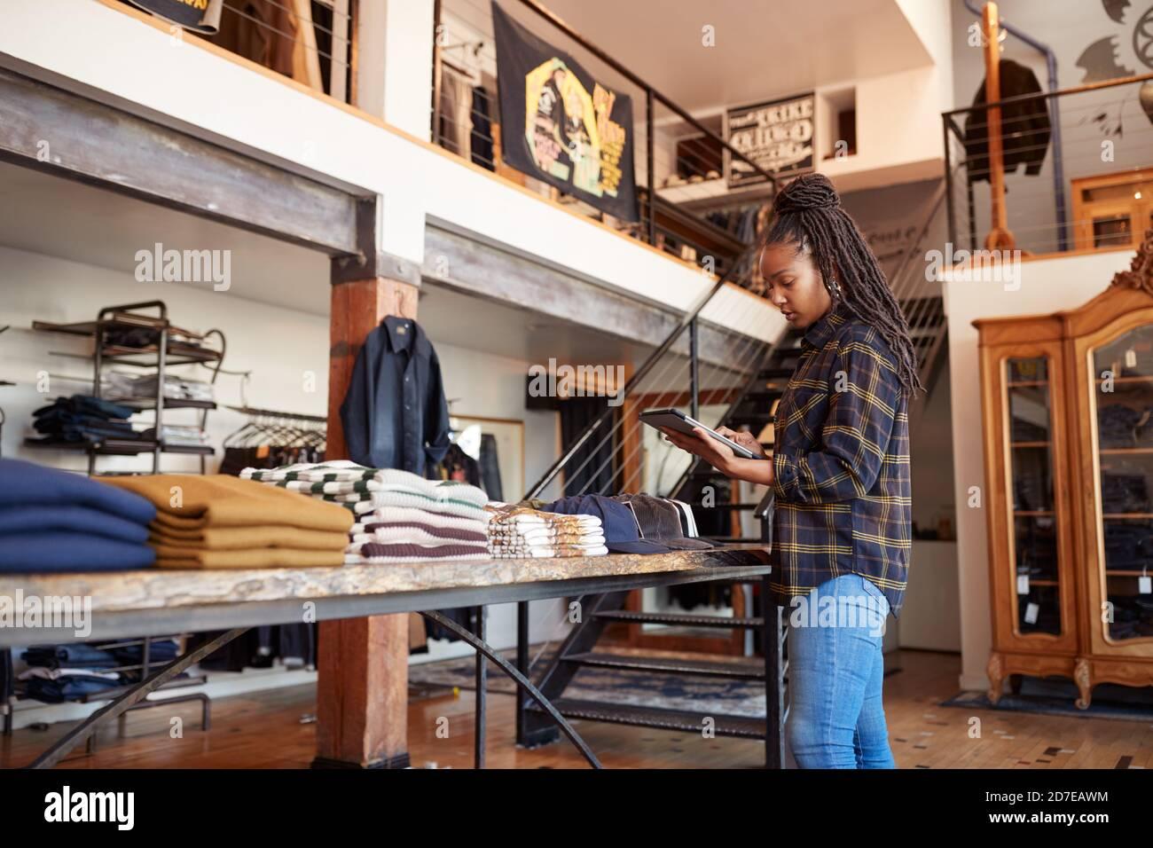 Femme propriétaire d'un magasin de mode utilisant une tablette numérique pour vérifier Stock dans la boutique de vêtements Banque D'Images
