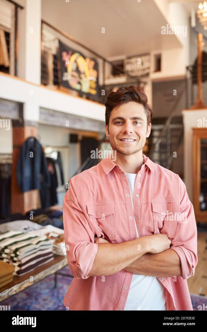 Portrait de l'homme souriant propriétaire de magasin de mode debout dans Avant du présentoir à vêtements Banque D'Images