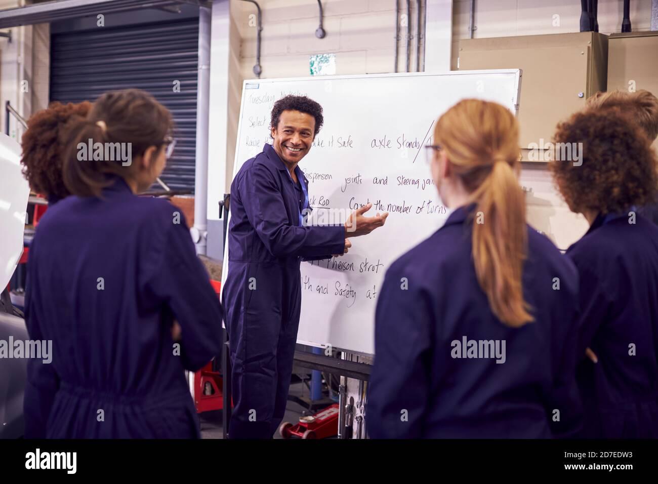 Tuteur masculin par Whiteboard avec des étudiants enseignant l'apprentissage mécanique automobile À l'université Banque D'Images