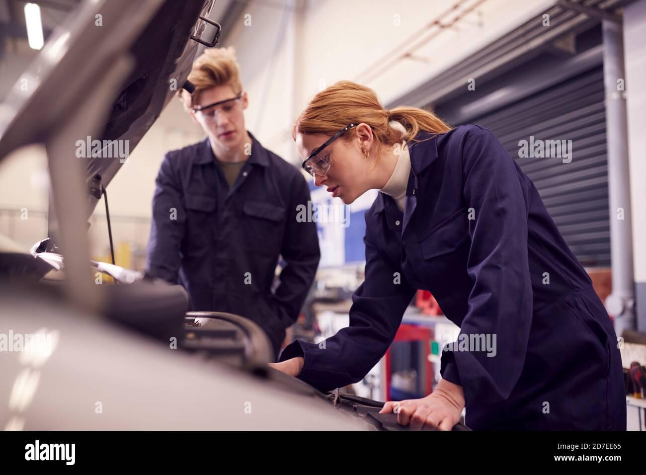 Étudiants hommes et femmes regardant le moteur de voiture sur Auto Cours d'apprentissage de mécanicien au Collège Banque D'Images