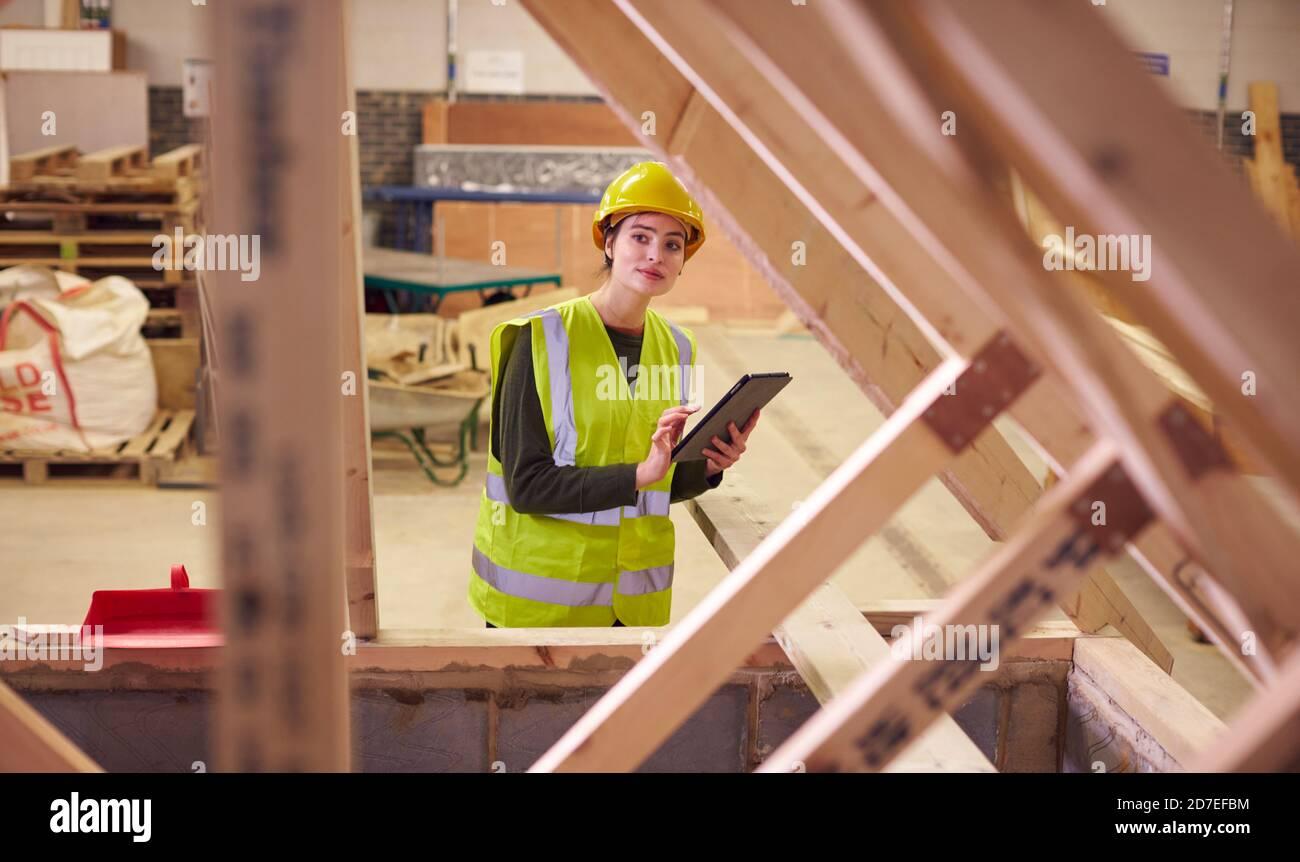 Inspecteur de sécurité féminin avec tablette numérique sur le chantier de construction Banque D'Images