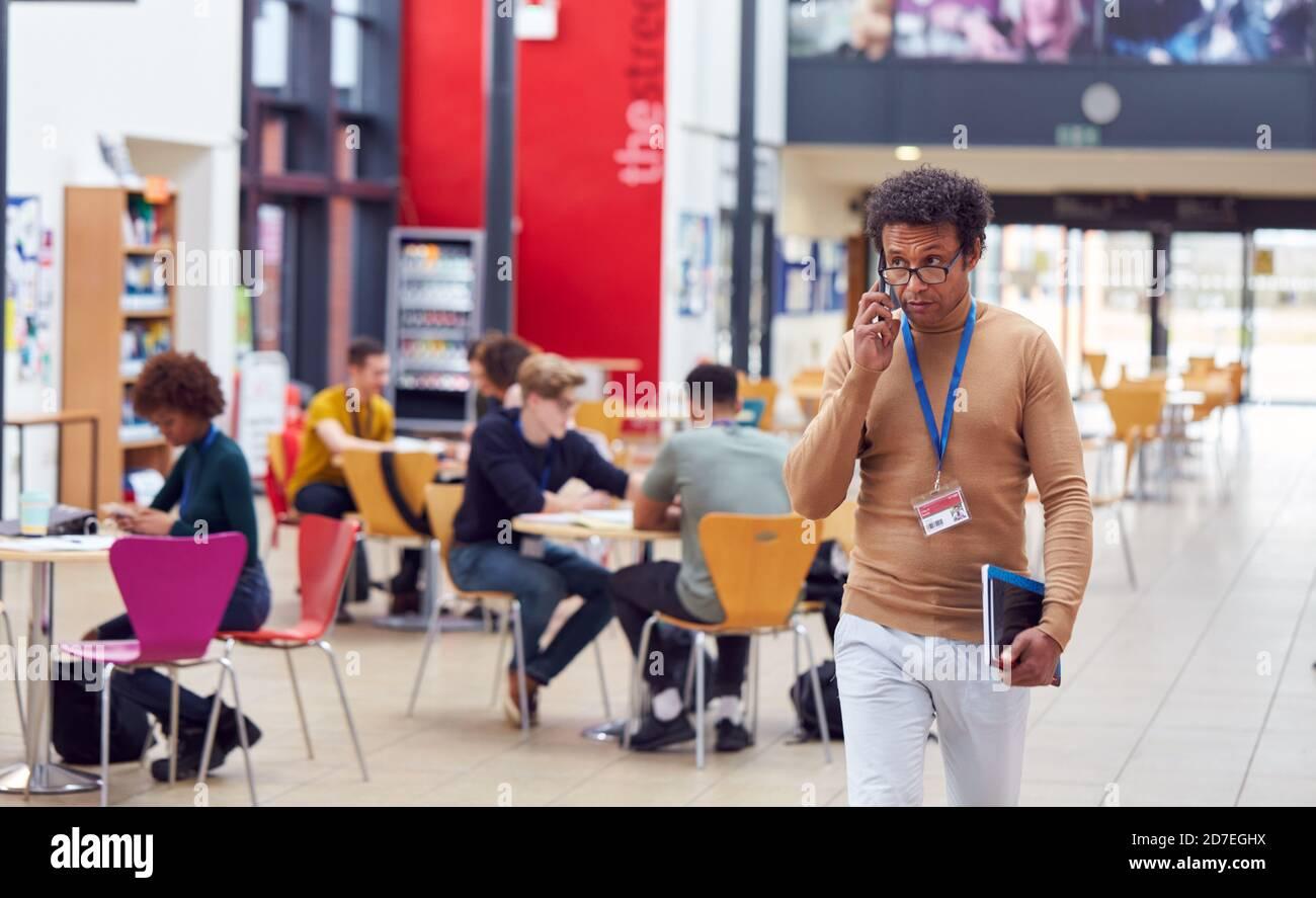 Zone commune du campus très fréquenté de l'université avec des étudiants travaillant à Tables et tuteur sur le téléphone Banque D'Images