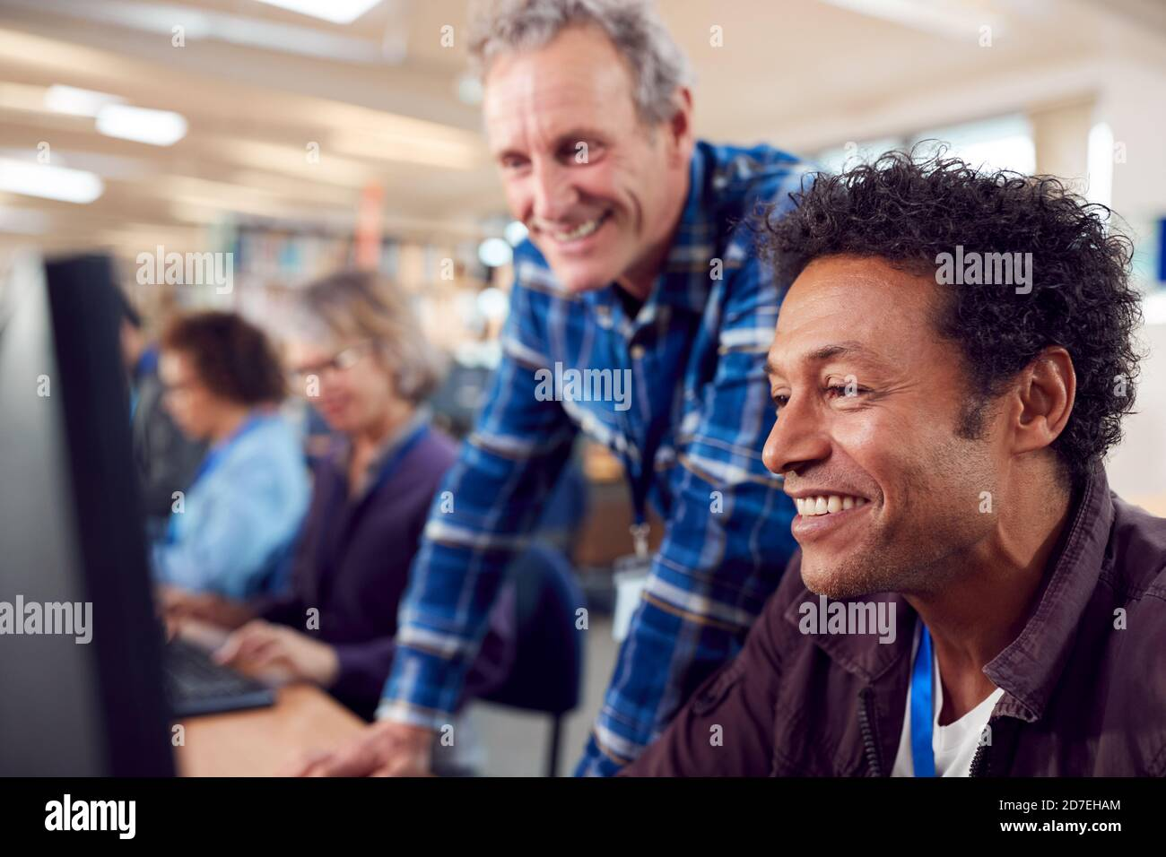 Professeur avec groupe d'étudiants adultes en classe de travail À la bibliothèque de l'université Banque D'Images
