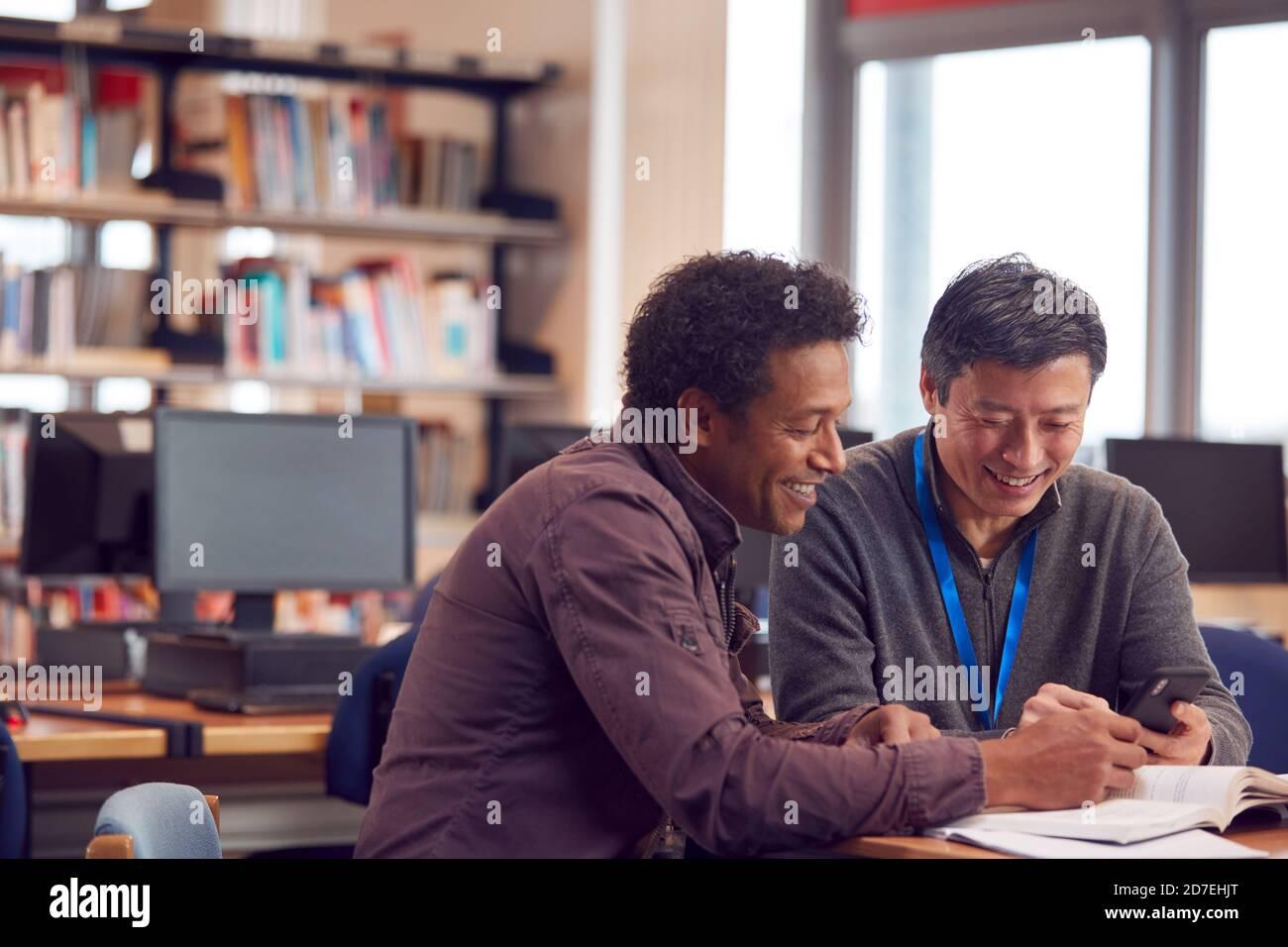 Professeur avec un étudiant adulte de sexe masculin mature utilisant un téléphone portable à Table de travail dans la bibliothèque du Collège Banque D'Images