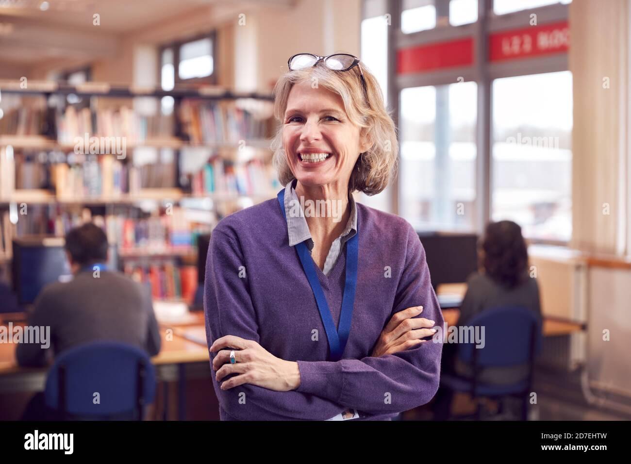 Portrait d'une enseignante ou d'une étudiante d'âge mûr à la bibliothèque avec Autres étudiants étudiant en arrière-plan Banque D'Images