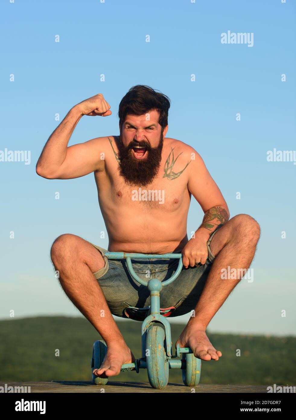 Guy tricycle d'équitation pour enfants. Drôle d'homme sur un vélo pour enfants. Vélo nerdy. Banque D'Images
