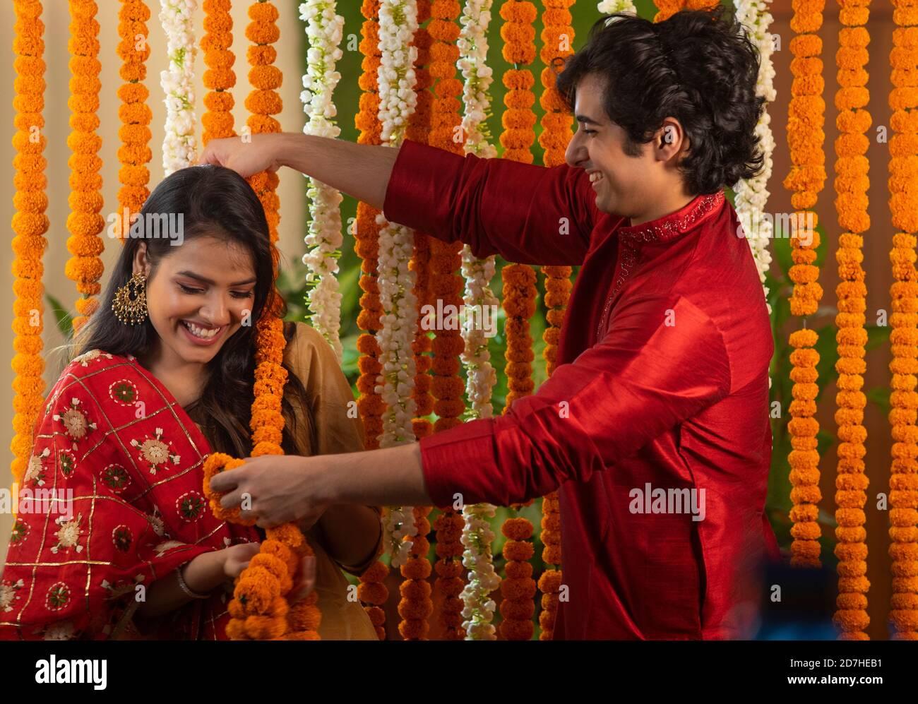jeune couple s'amusant les uns avec les autres tout en décorant avec guirlandes de fleurs Banque D'Images