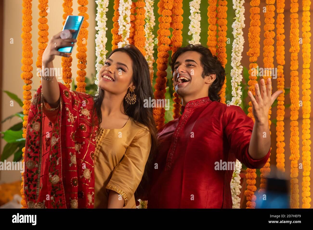 Un jeune couple qui clique sur un selfie ensemble alors qu'il pose avec charme Banque D'Images
