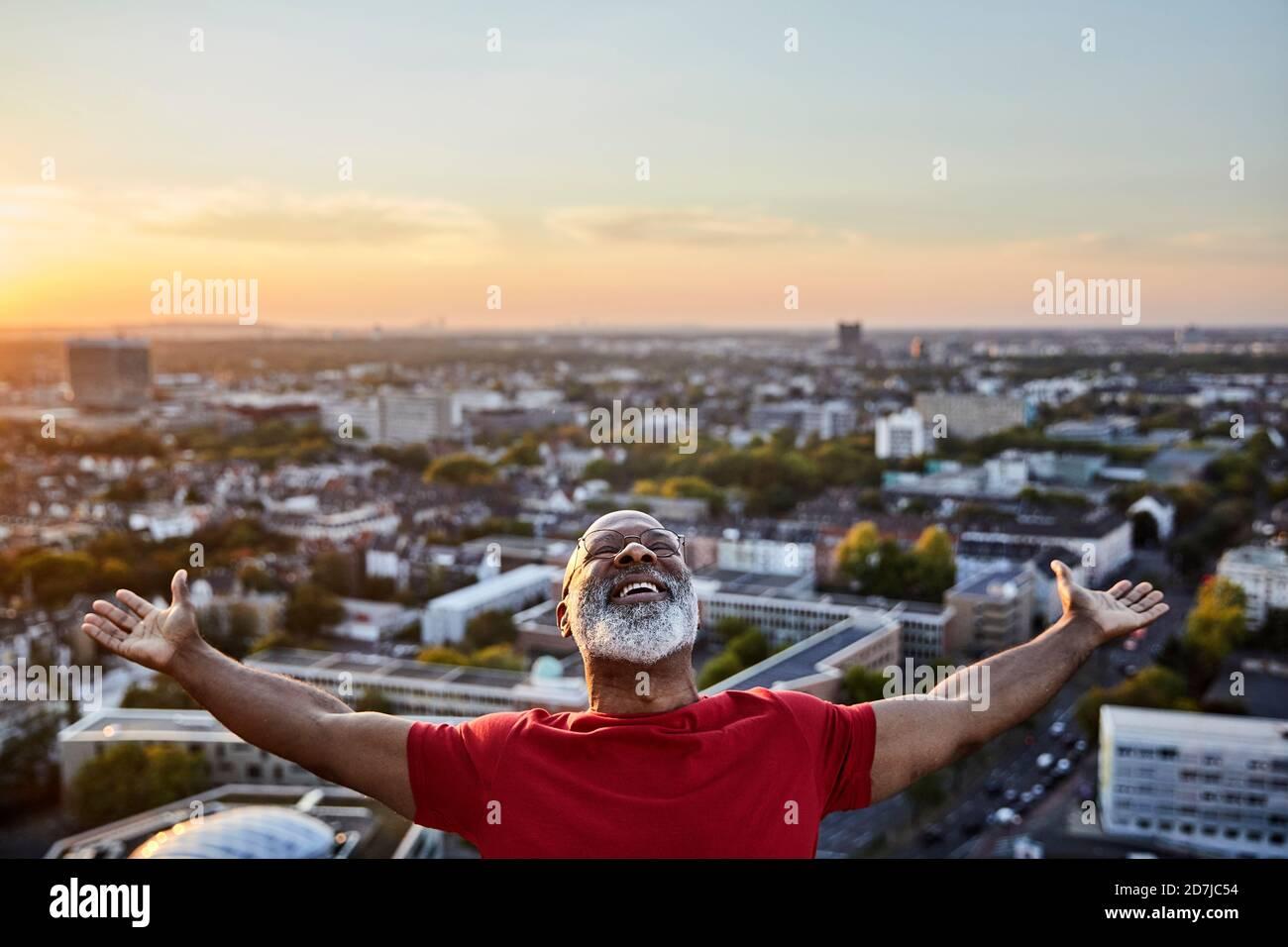 Homme à barbe heureux avec les bras étirés tout en se tenant debout sur le bâtiment terrasse en ville au coucher du soleil Banque D'Images