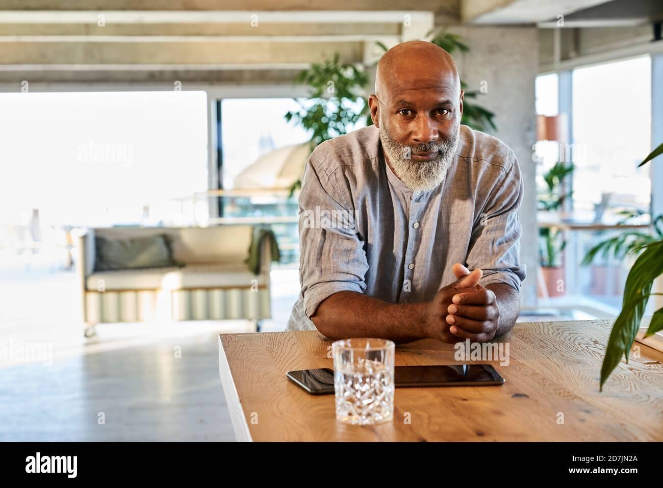 Homme bald confiant avec les mains clastées s'inclinant sur la table à sur le toit Banque D'Images