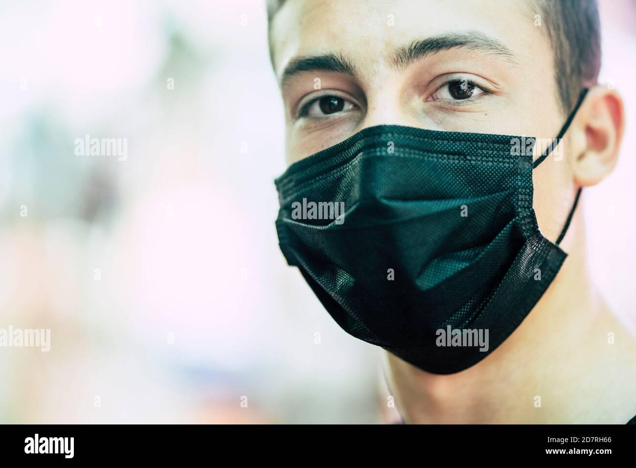 Jeune garçon caucasien adolescent ans porter un masque de protection pour Covid-19 urgence du coronavirus - portrait des personnes en période de confinement et d'épidémie pandémie c Banque D'Images
