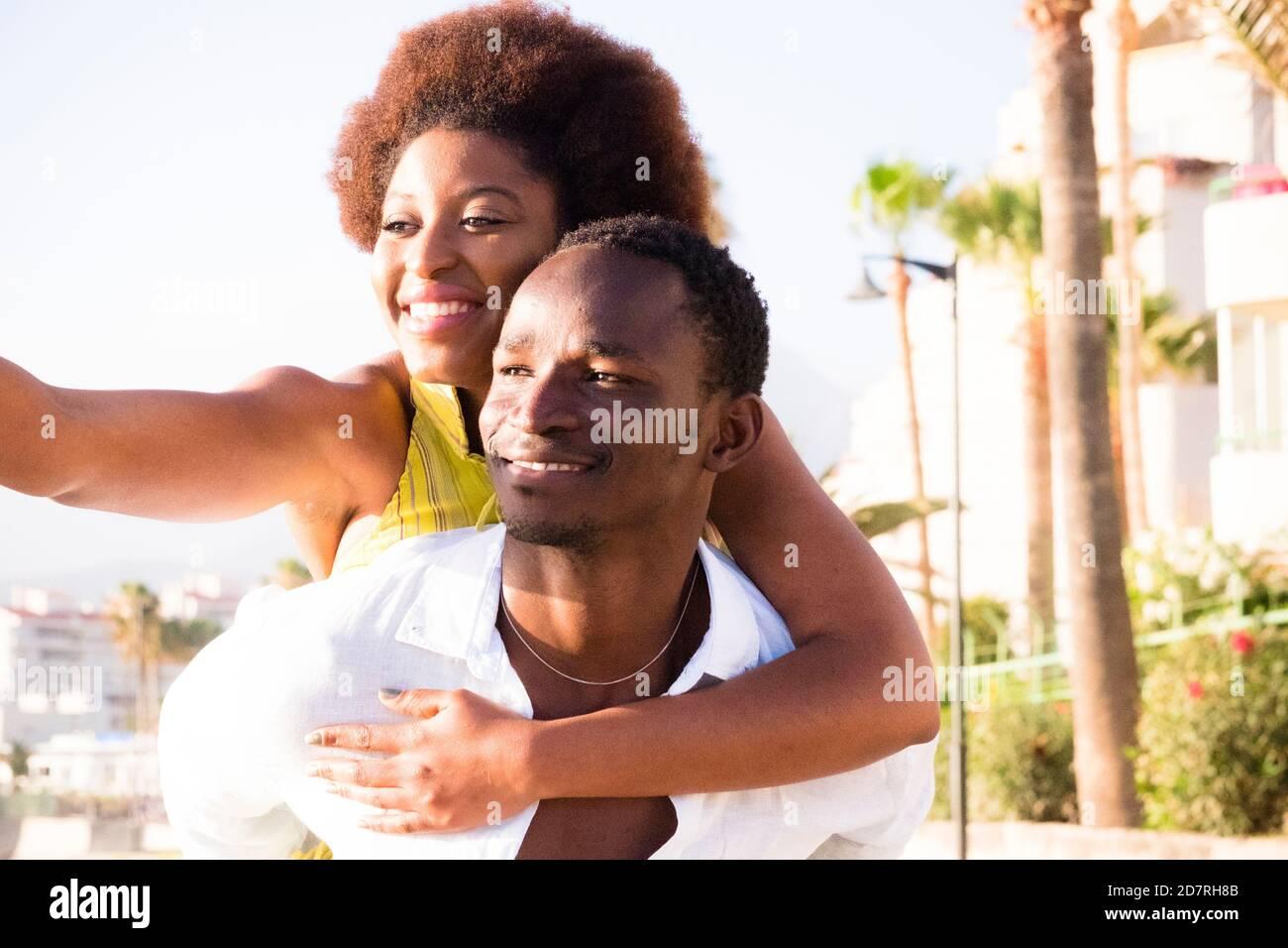 Les jeunes couples noirs s'amusent et rient en appréciant le activités de loisirs en plein air ensemble - homme portant une belle fille africaine avec des cheveux ethniques Banque D'Images