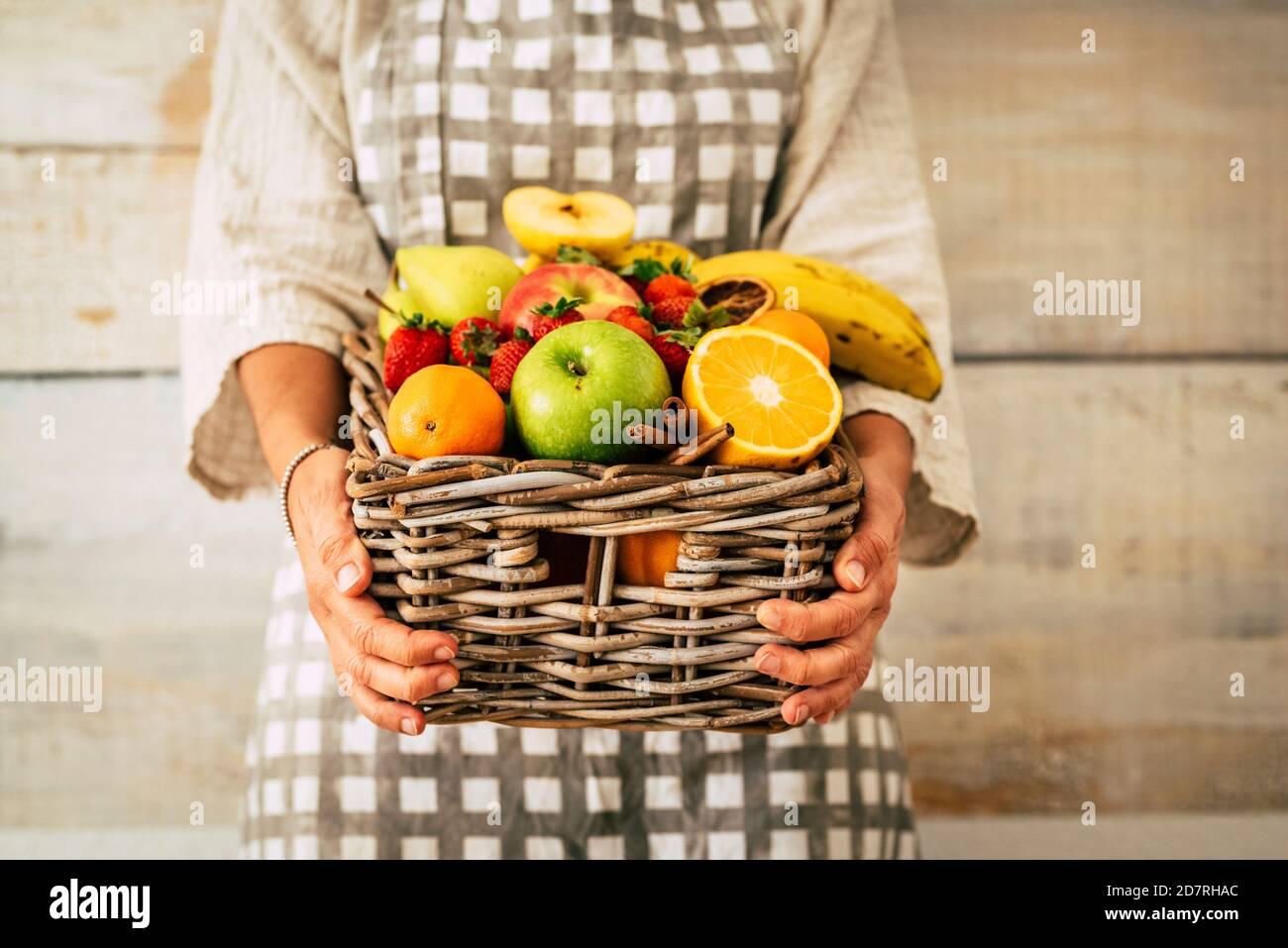 Seau de fruits frais entroué par une femme adulte avec fond de mur - concept de perte de poids et de commerce de fruits - agriculture et vie professionnelle des agriculteurs Banque D'Images