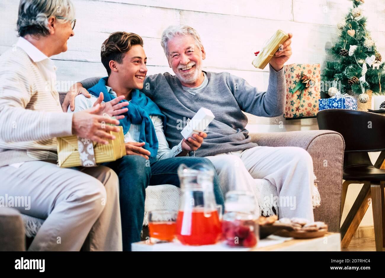 Une famille joyeuse fête ses vacances et la veille de noël ensemble plaisir et partage de cadeaux - jeune garçon avec un aîné les grands-pères s'amusent avec Banque D'Images