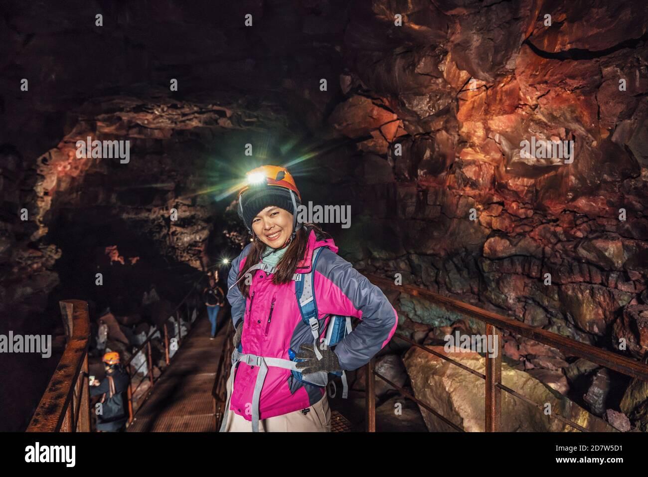Une femme voyageur explore le tunnel de lave en Islande. Raufarholshellir est un beau monde caché de caverne. C'est l'une des plus longues et des plus connues lave Banque D'Images