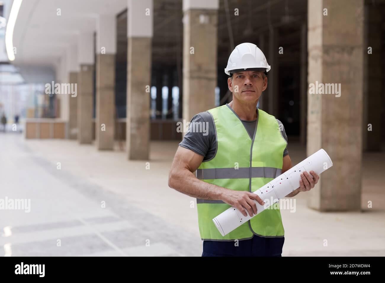 Portrait à la taille de l'ouvrier de construction professionnel tenant des plans et regardant l'appareil photo tout en se tenant dans un immeuble de bureau, espace de copie Banque D'Images