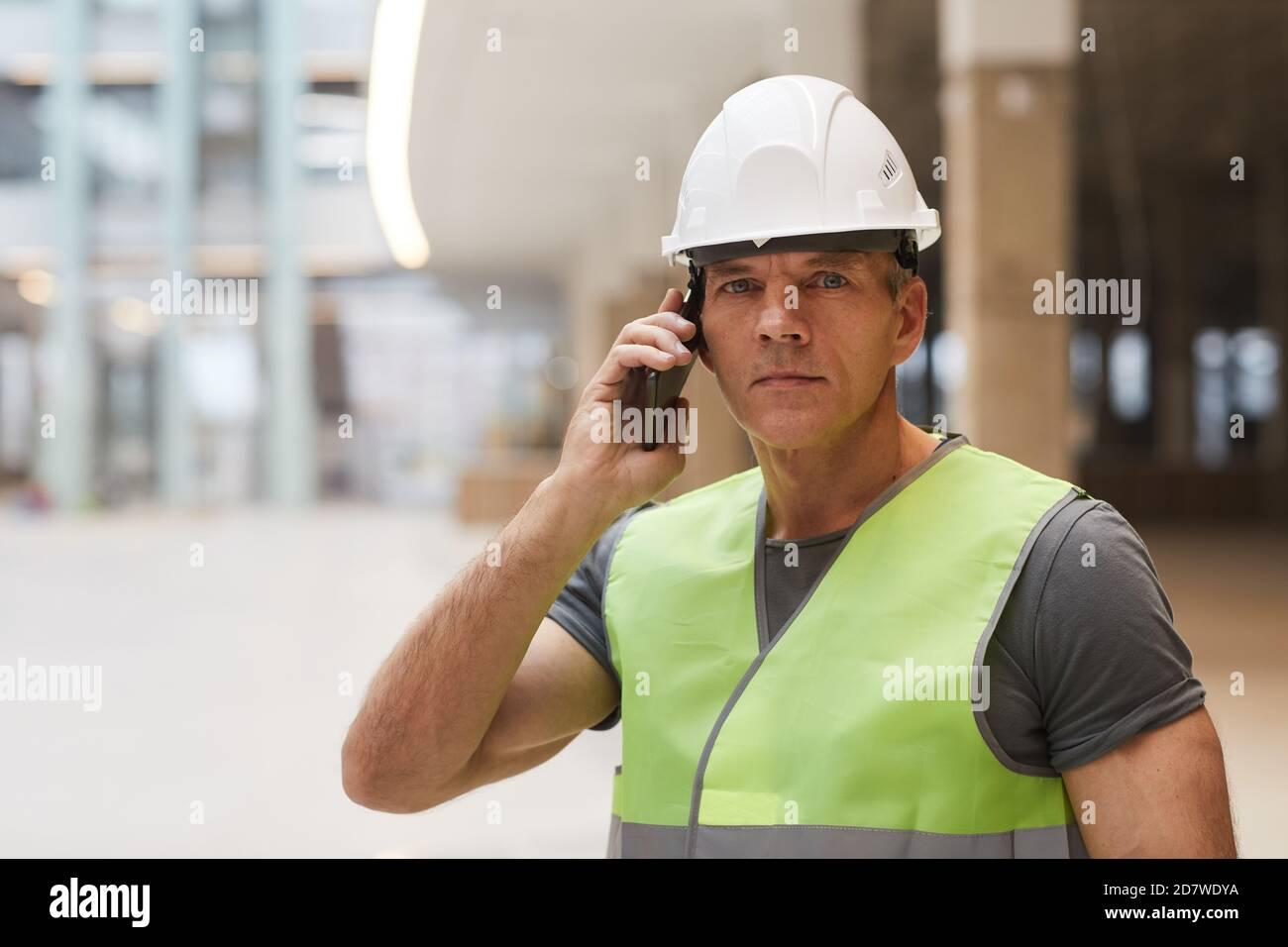 Portrait d'un travailleur de la construction professionnel parlant au téléphone et regardant l'appareil photo tout en se tenant sur le chantier, espace de copie Banque D'Images