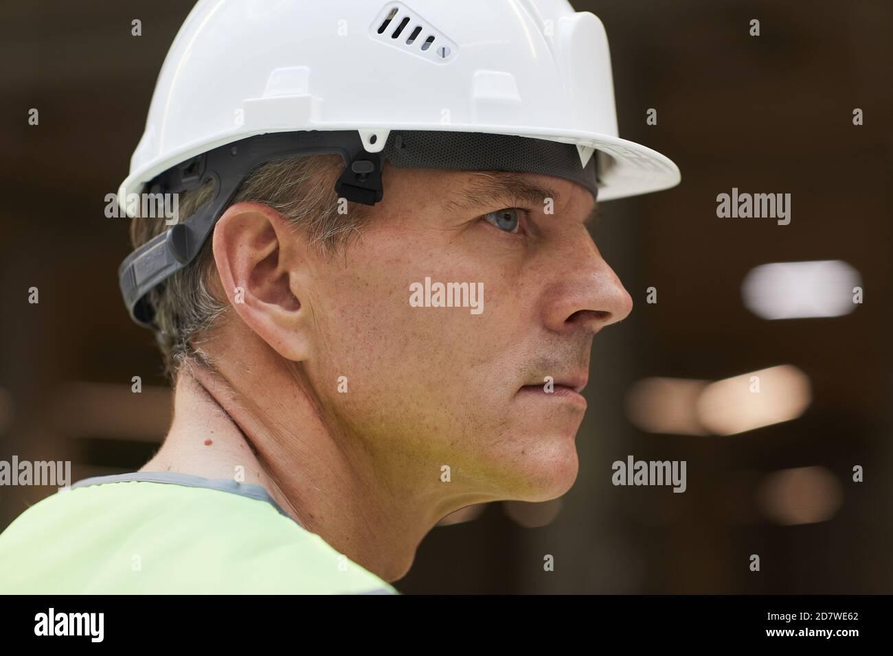 Portrait de côté d'un ouvrier de construction professionnel portant un casque et regardant loin, espace de copie Banque D'Images