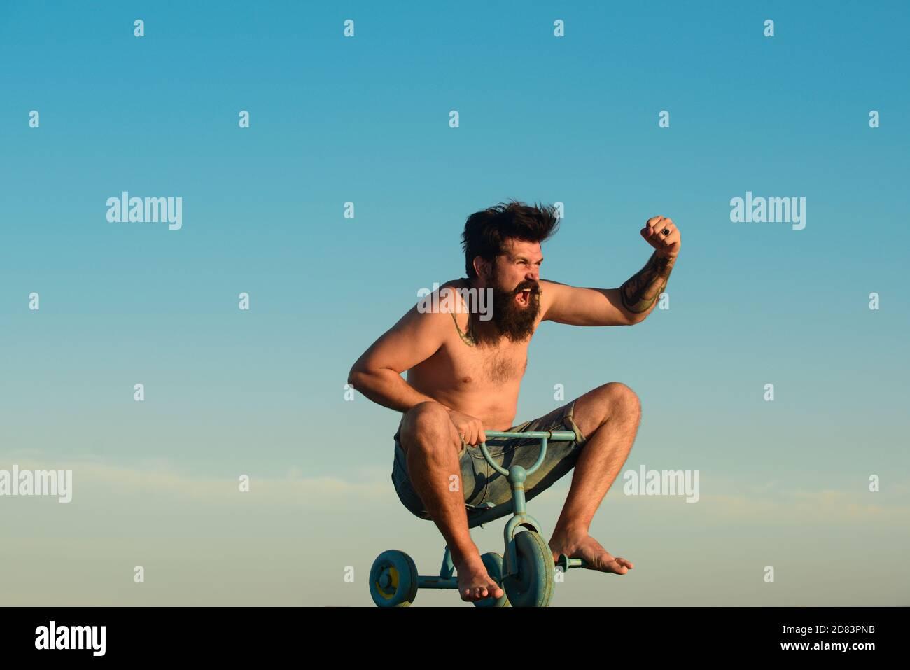 Un jeune homme excités qui fait un petit vélo et qui fait des gestes de bonheur. Drôle d'homme fou à vélo. Guy tricycle d'équitation pour enfants. Banque D'Images
