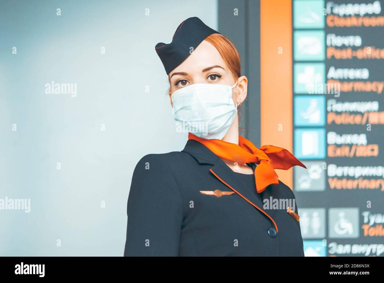 Gros plan du magnifique agent de vol Red Head portant un masque de protection et restez près du panneau de départ et d'arrivée. Covid-19 Outbreak Travel Restrictio Banque D'Images