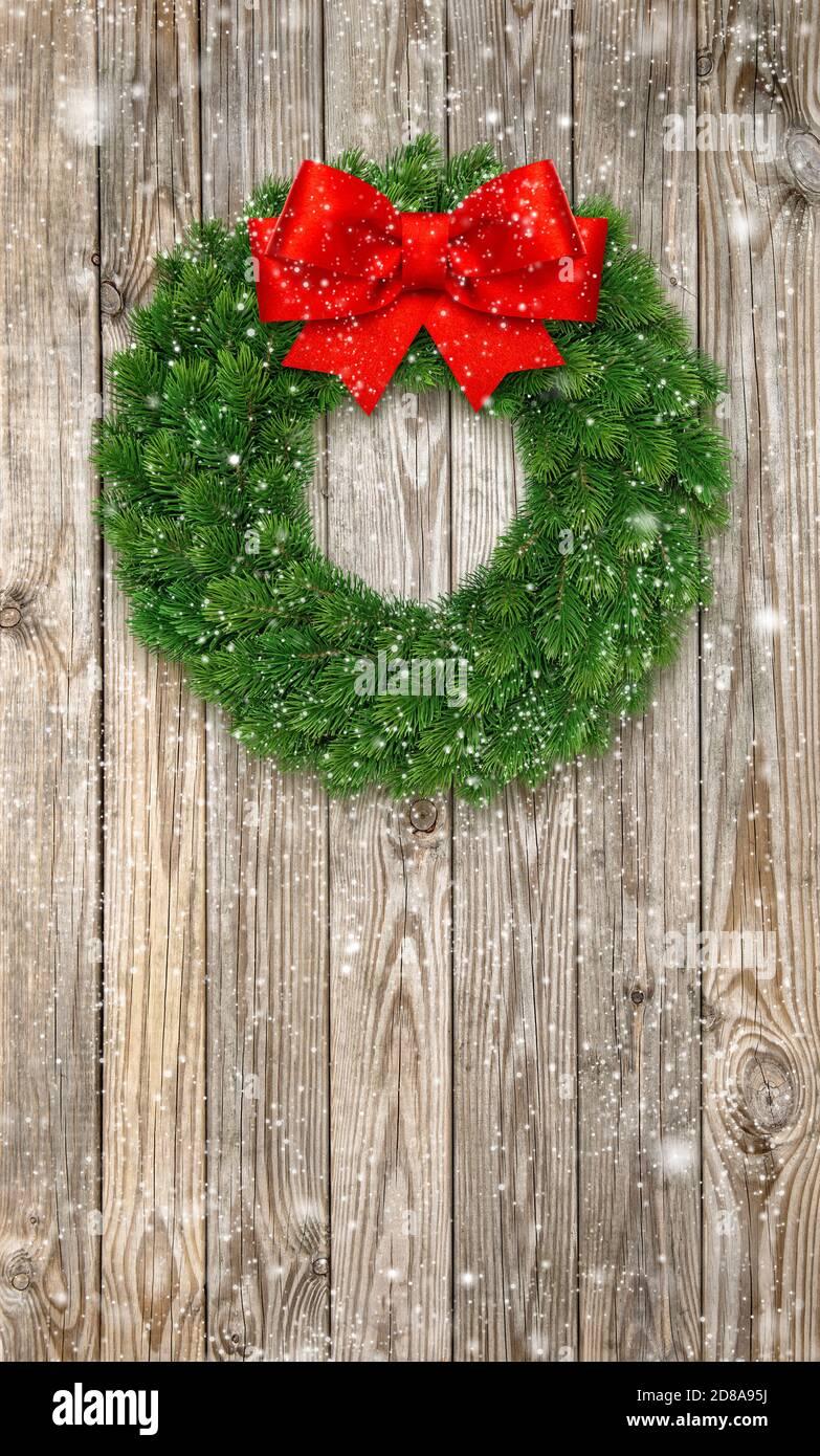Couronne de Noël avec noeud en ruban rouge et effet neige tombant Banque D'Images