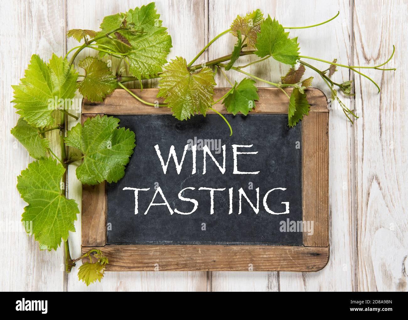 Dégustation de vins. Tableau noir avec décoration de feuilles de vigne vertes Banque D'Images