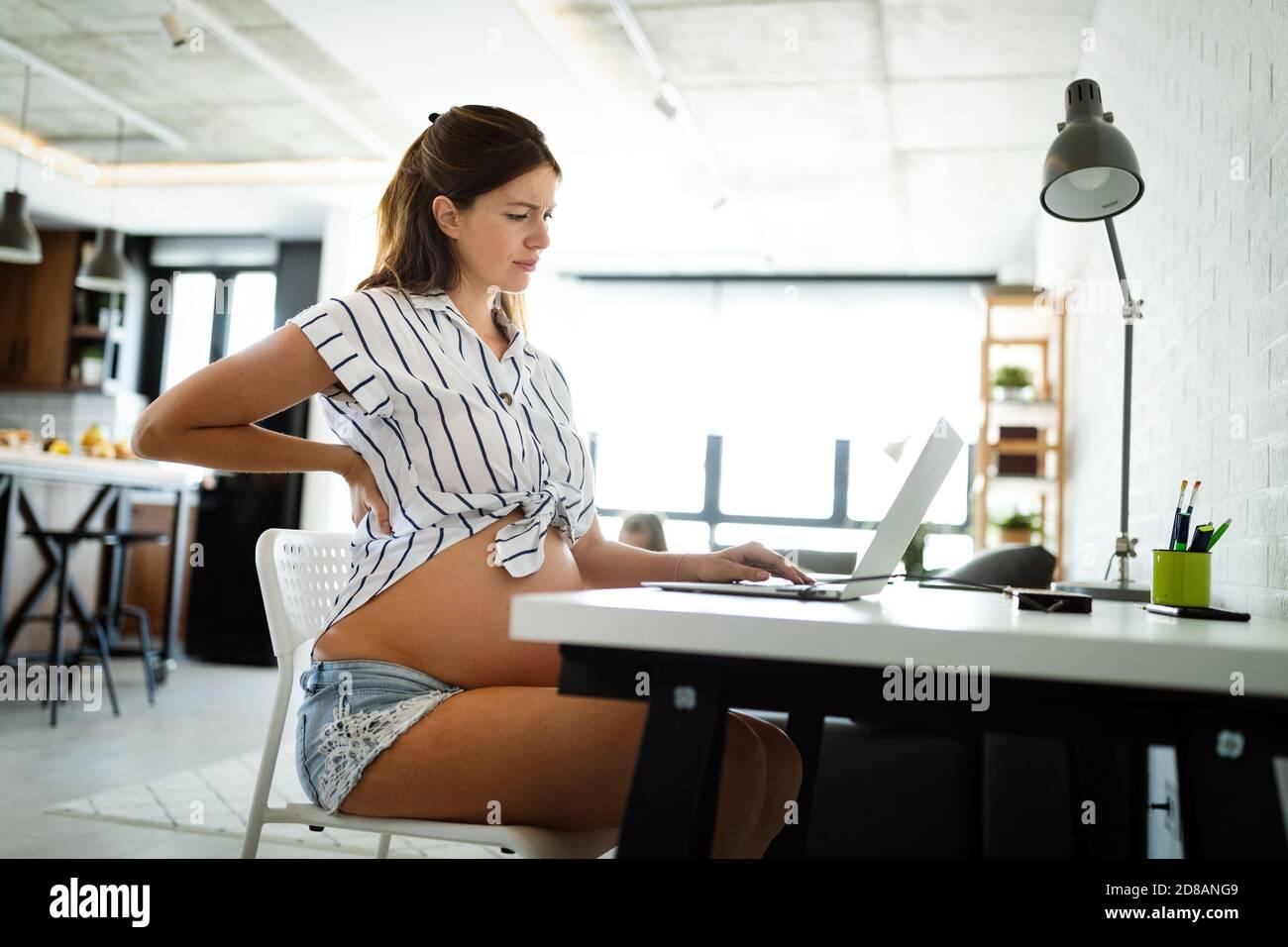 Femme enceinte fatiguée le travail à domicile sur ordinateur Banque D'Images