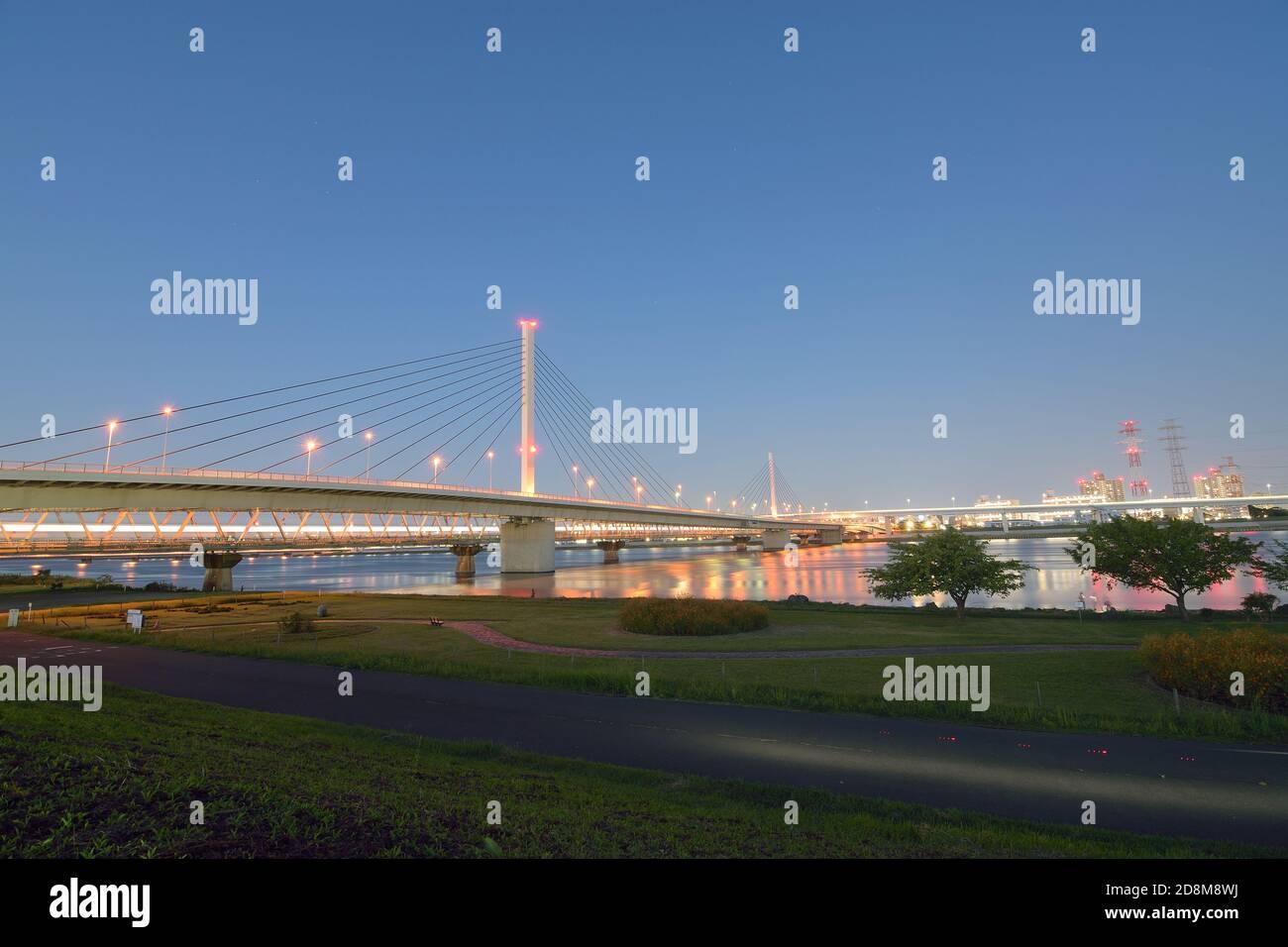 Paysage urbain de longue exposition de pont suspendu dans le ciel de crépuscule arrière-plan Banque D'Images