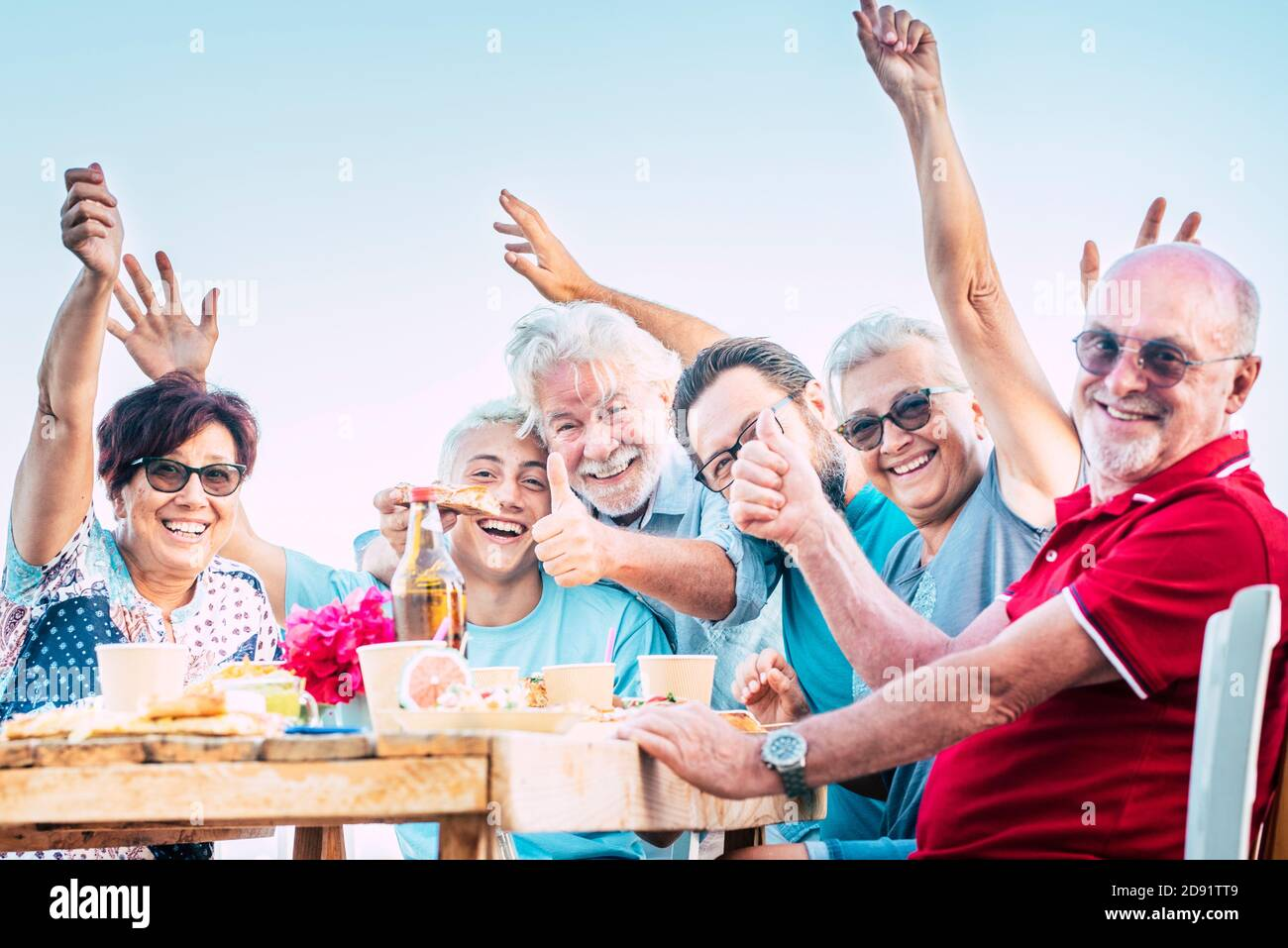Groupe de personnes famille s'amuser et profiter de la fête en plein air - les hommes et les femmes caucasiens rient autour d'une table en bois avec plats et boissons - wi d'anniversaire Banque D'Images
