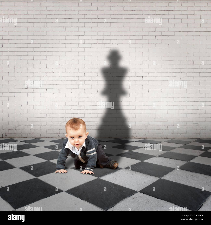 petit garçon avec une ombre très grande sur un sol à carreaux Banque D'Images