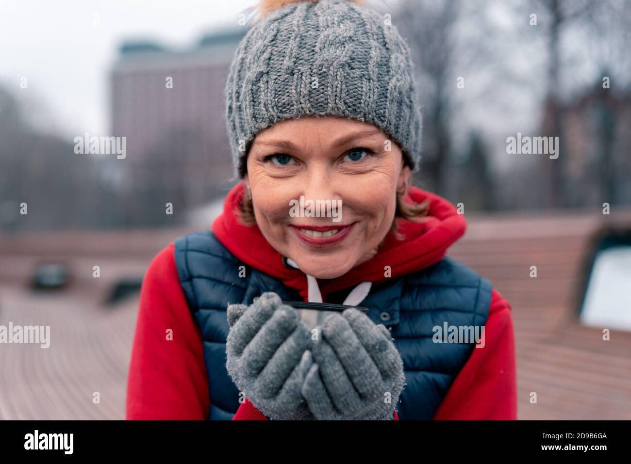 Belle femme mature Drinking Hot Tea de Thermos dans le parc et de détente après l'entraînement de fitness actif avec des amis. Style de vie actif des personnes d'âge moyen Banque D'Images