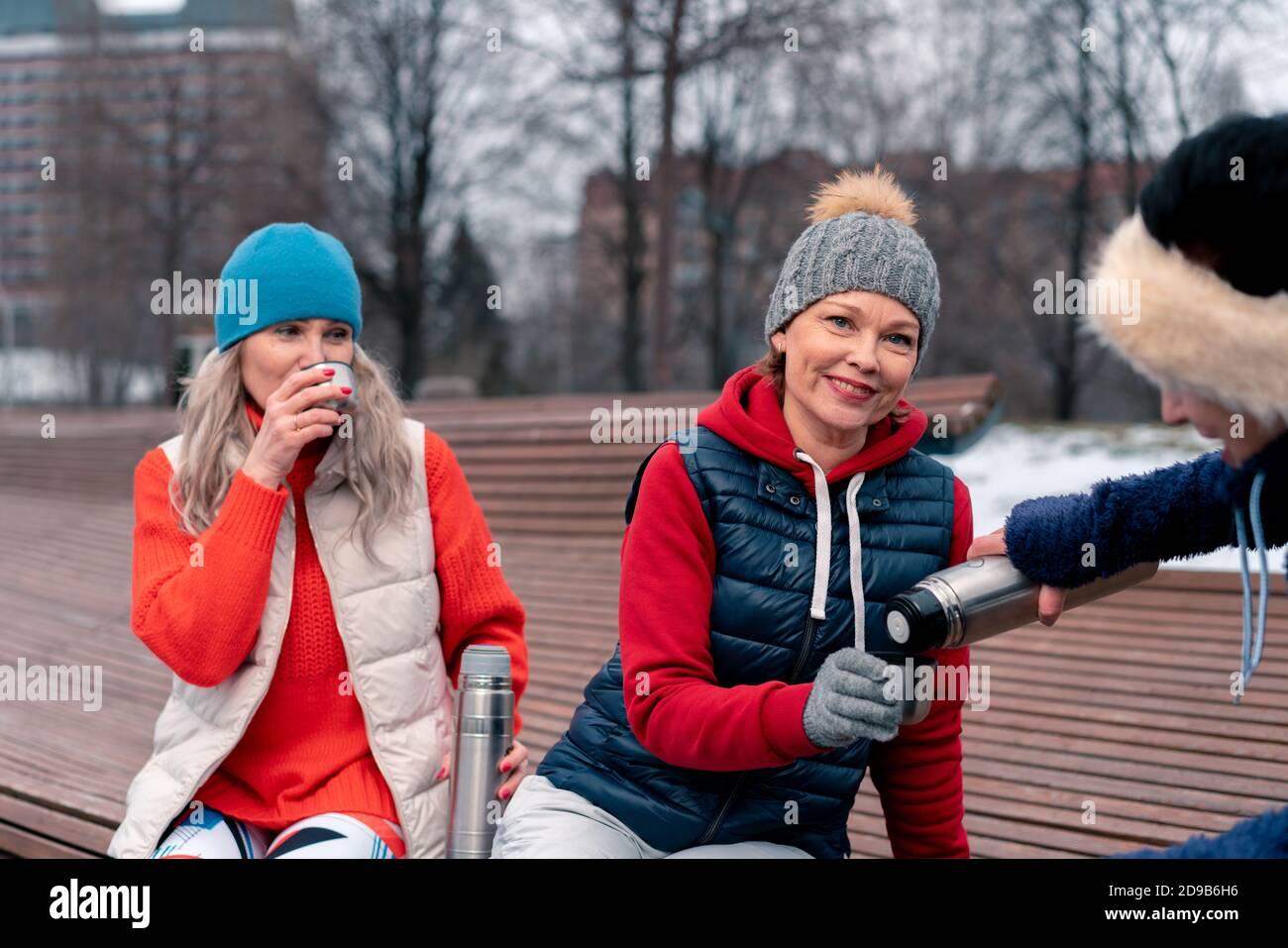 Une femme mûre verse du thé chaud de Thermos à son ami après un entraînement de fitness actif dans le parc. Style de vie actif et joyeux des personnes d'âge moyen. Banque D'Images
