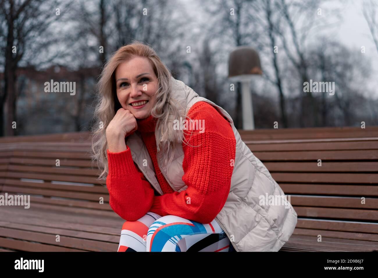 Blond Mûr Femme Smiling Et Assis Sur Le Banc Dans Le Parc Moderne Après Des Exercices Actifs À L'Extérieur. Style De Vie Des Personnes Âgées. Sport Et Relaxe Banque D'Images