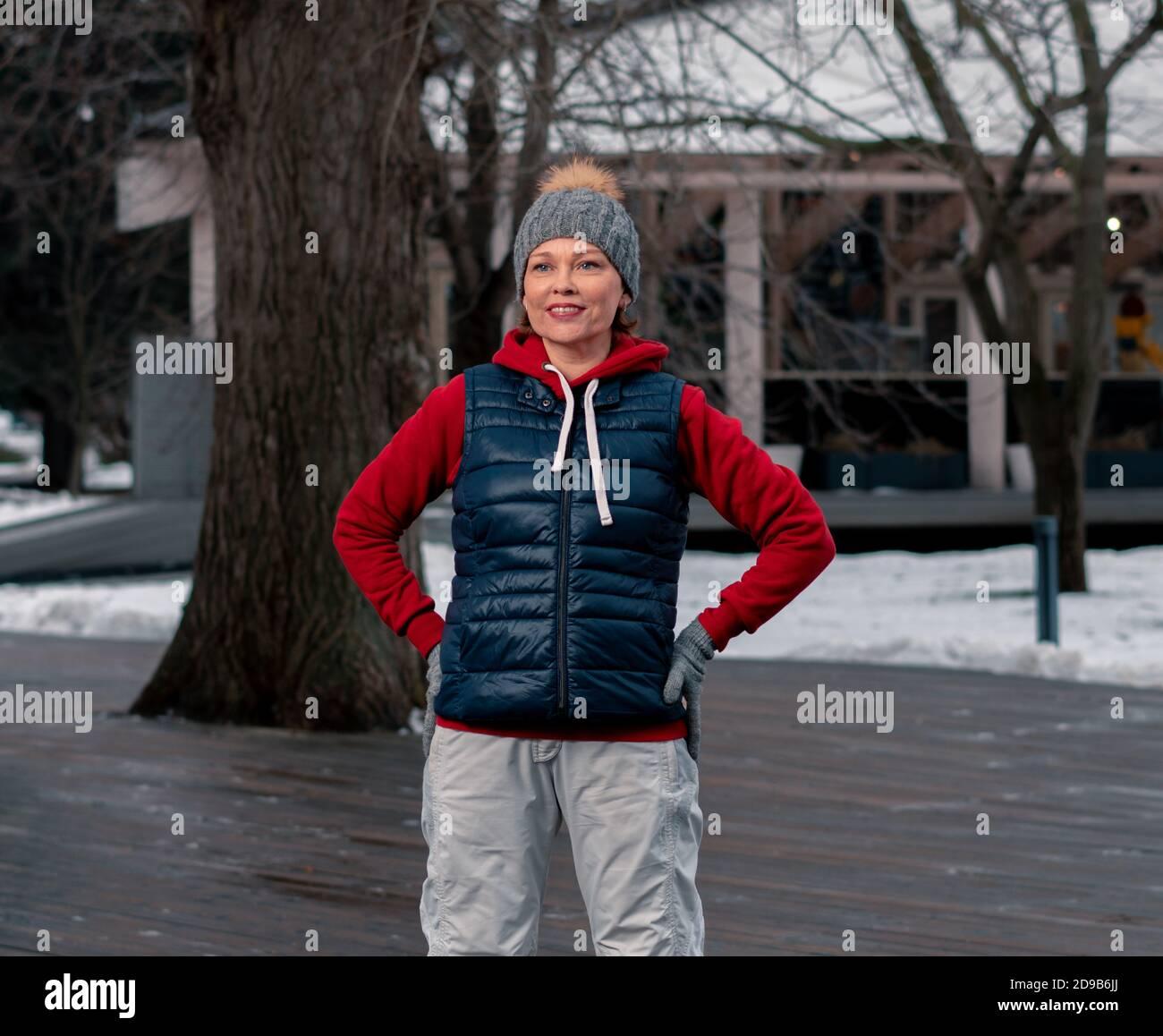Belle femme mûre IWarming au parc. Temps froid de l'année. Un mode de vie actif et sain au Moyen-âge. Banque D'Images