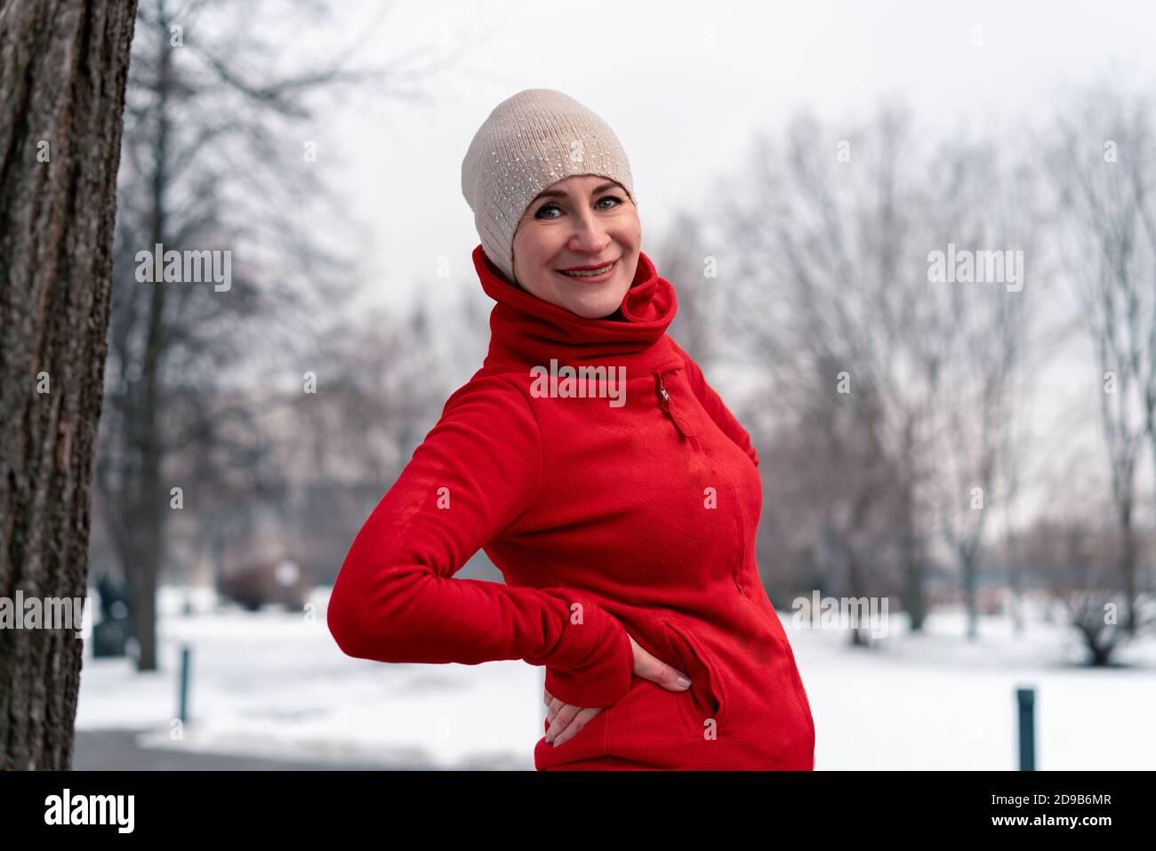 Belle femme mature dans Red Sportswear après avoir fait du jogging et de la course à l'extérieur avec Park at Background. Temps froid de l'année. Actif et sain Banque D'Images
