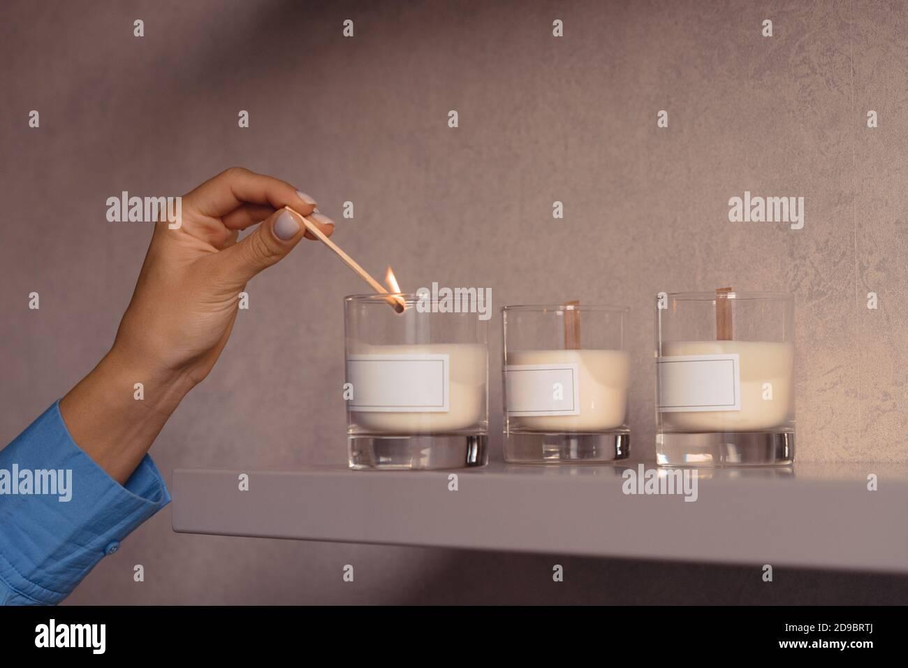 Woan éclairez la bougie parfumée en verre avec une étiquette blanche vierge dans sa chambre pour la détente. Aromathérapie Banque D'Images